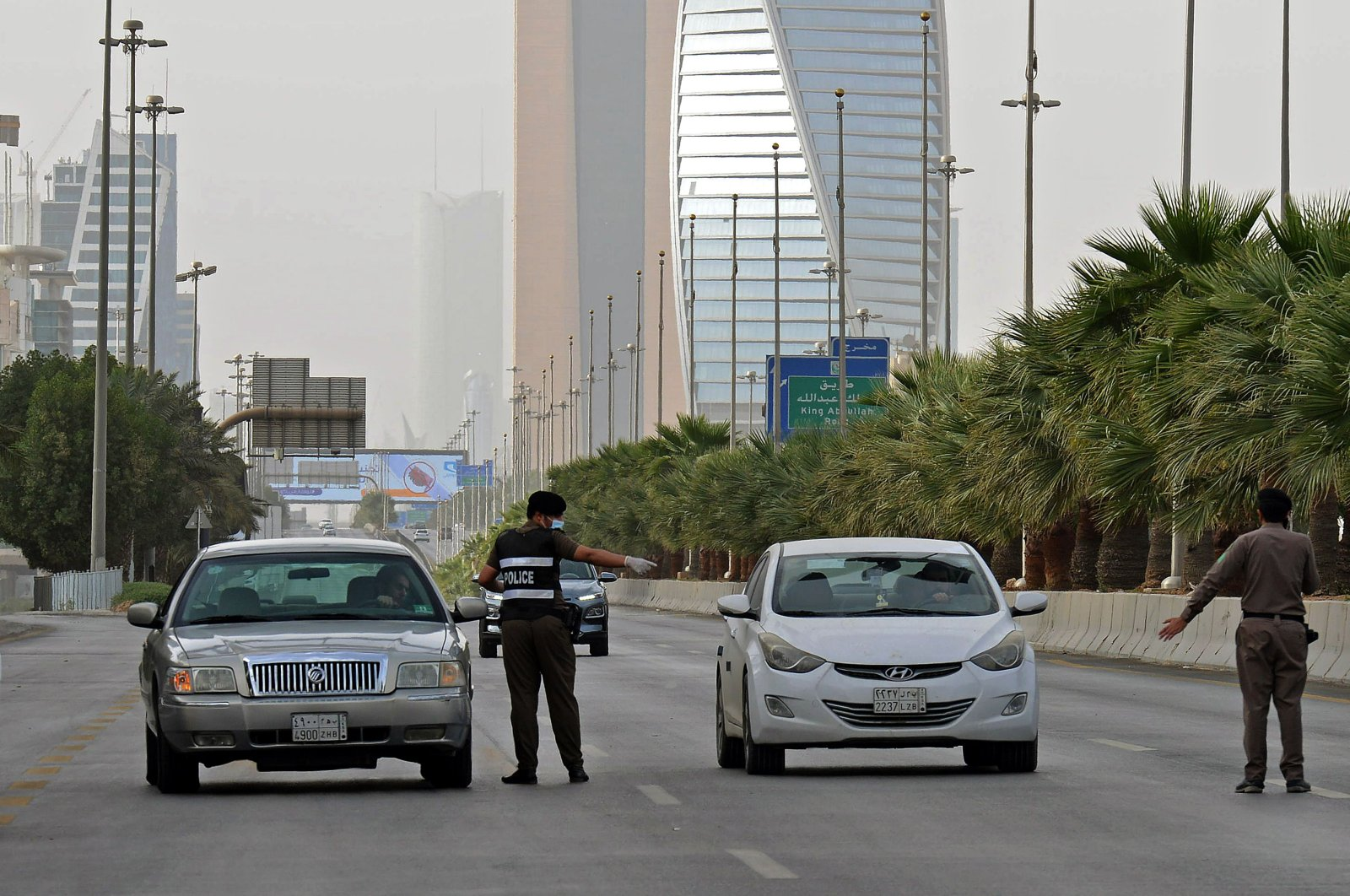 Policemen are seen manning a checkpoint in King Fahad Street in Riyadh, Saudi Arabia, Thursday, March 26, 2020. (AFP Photo)