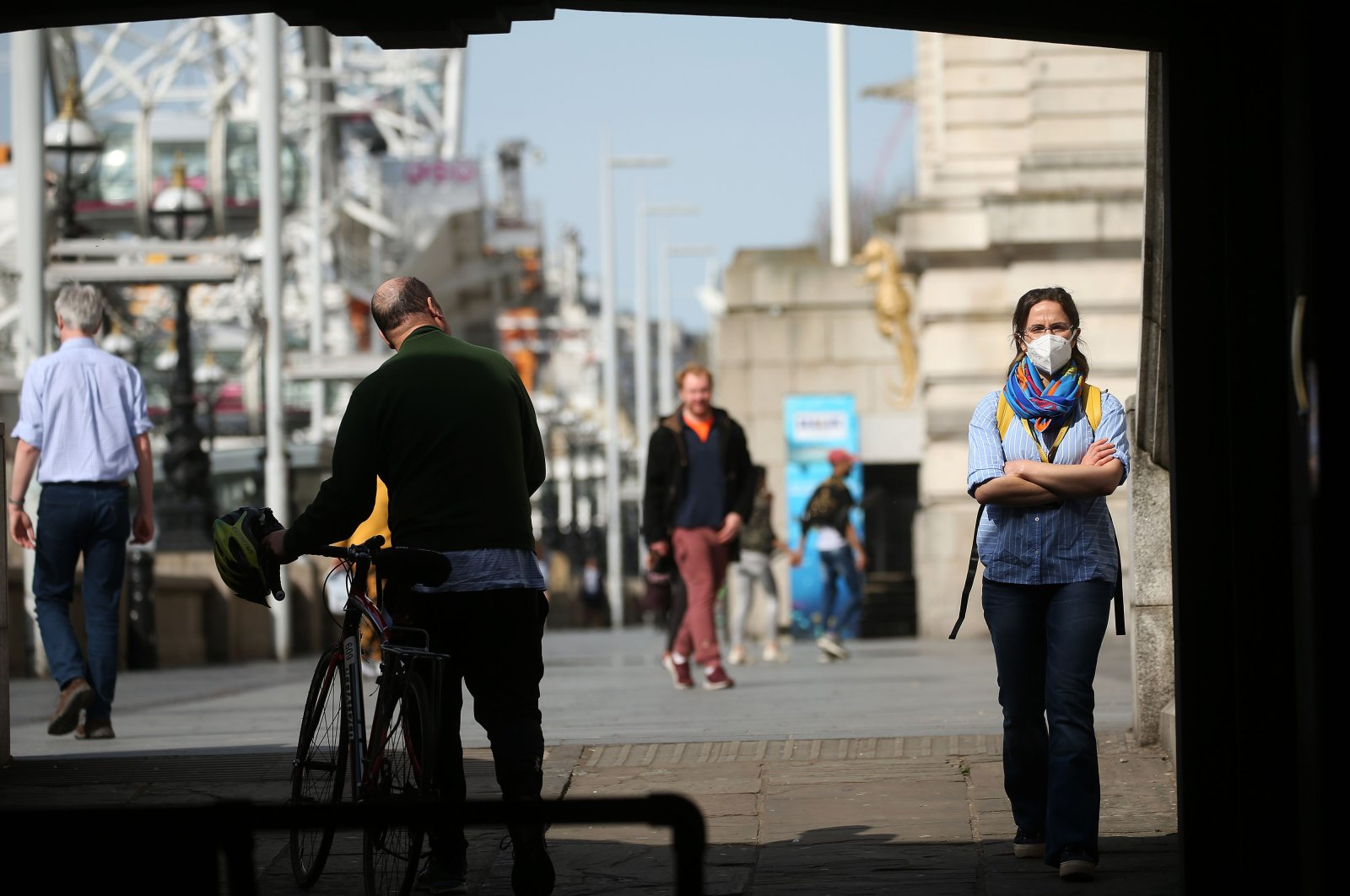 A woman wearing a face mask as a precautionary measure against COVID-19, walks past a cyclist on the South Bank, by the River Thames in central London on April 7, 2020, as life in Britain continues during the nationwide lockdown to combat the novel coronavirus pandemic. (AFP Photo)