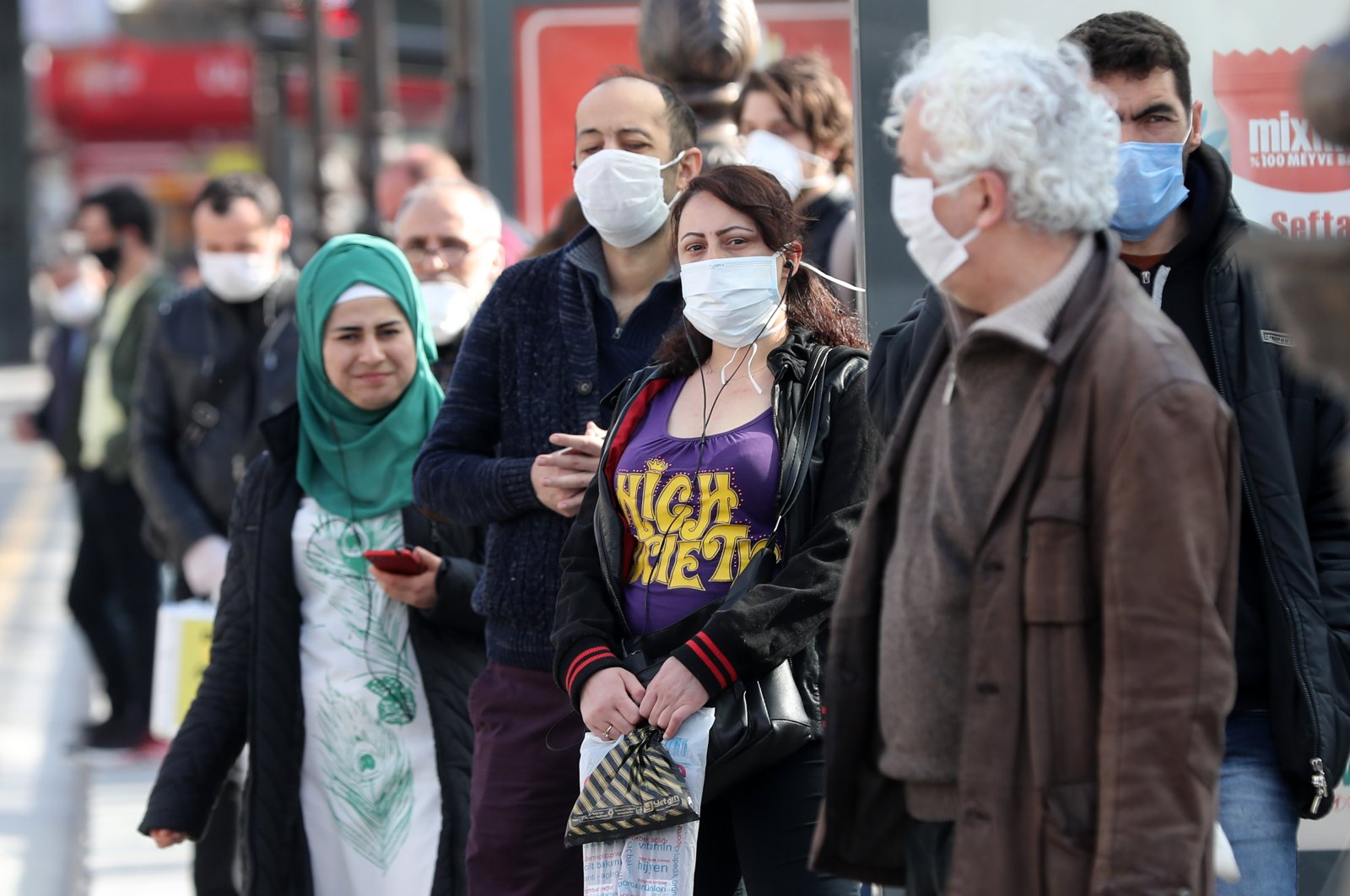 People wearing protective masks wait at a bus stop in Ankara, April 6, 2020. (AFP Photo)