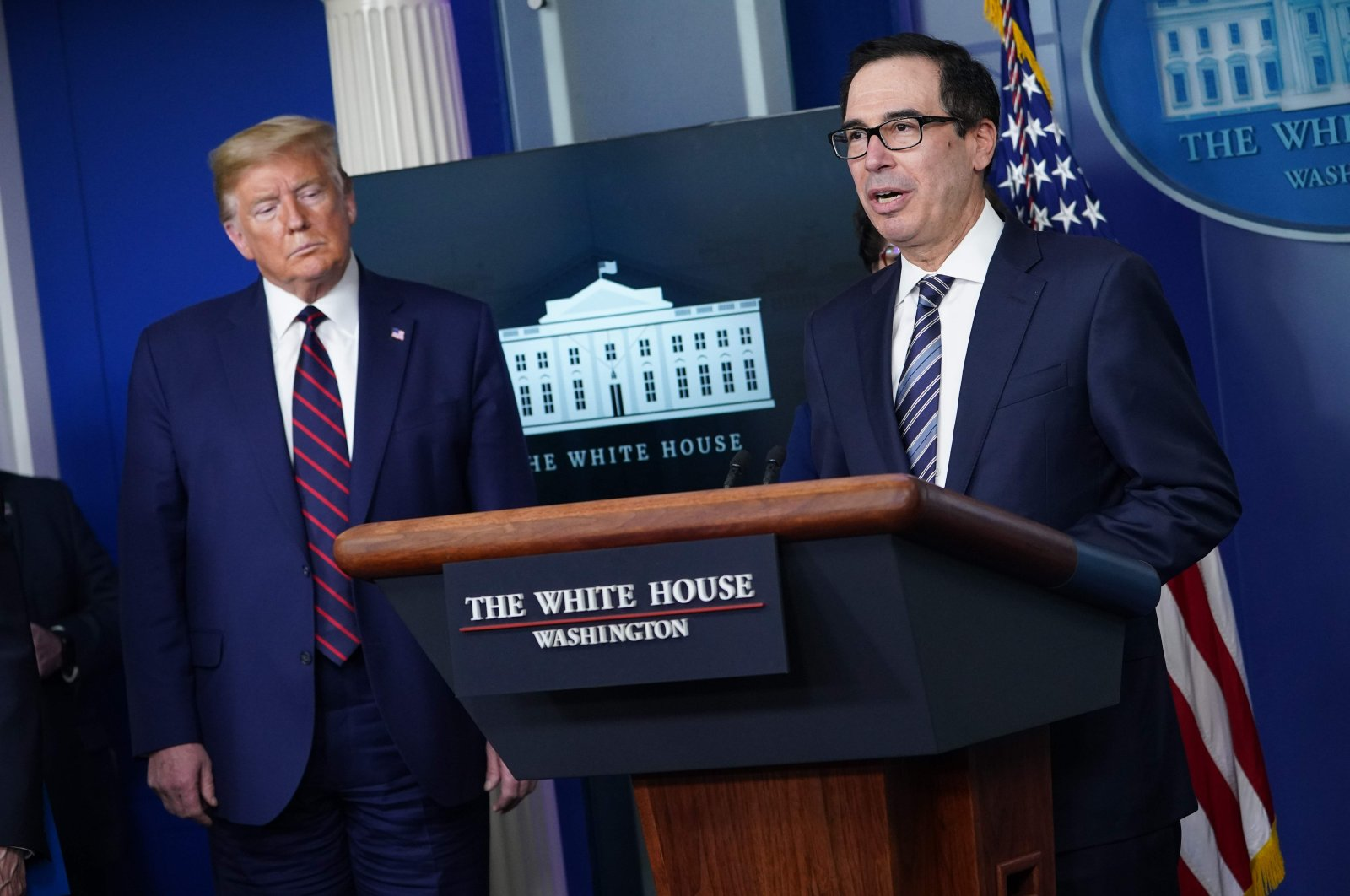 U.S. Secretary of the Treasury Steven Mnuchin speaks while U.S. President Donald Trump listens during the daily briefing on the novel coronavirus in the Brady Briefing Room at the White House, Washington, D.C., Thursday, April 2, 2020. (AFP Photo)