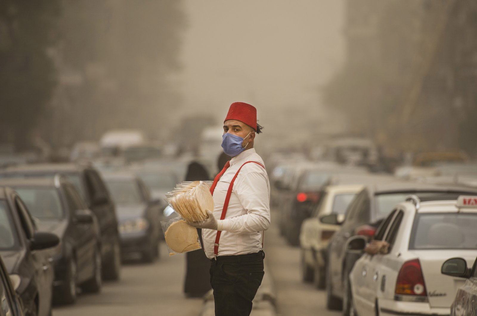 A street vendor wearing a protective face mask stands on a street between lines of cars during a sandstorm in Cairo, Egypt, Sunday, April 5, 2020. (EPA Photo)