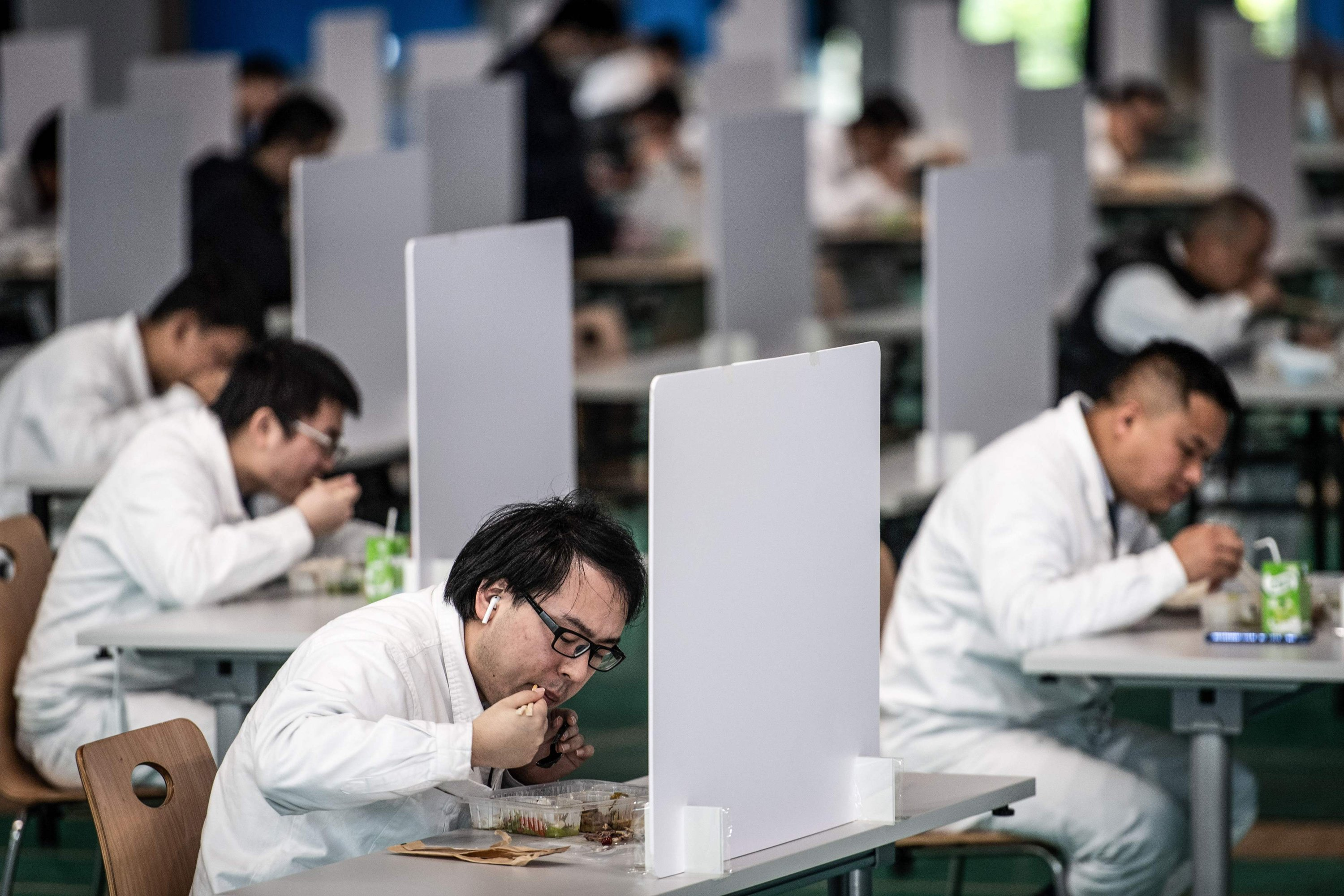 Employees eat during a lunch break at a Dongfeng Honda auto plant in Wuhan, Hubei province, China on Tuesday, April 7, 2020. (AFP Photo)