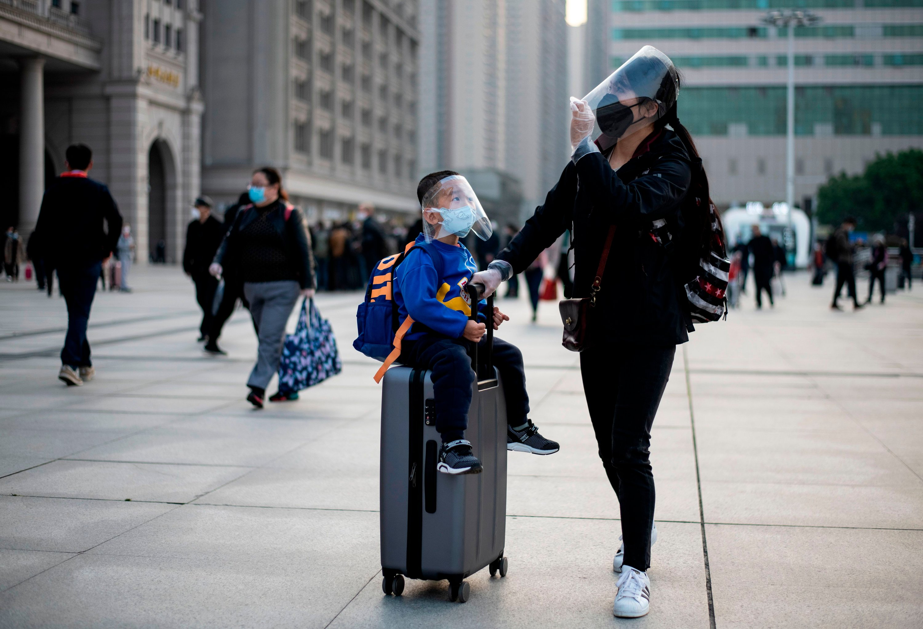 A woman and her child wearing face masks arrive at Hankou railway station to take one of the first trains leaving Wuhan, Hubei province, China early Wednesday, April 8, 2020. (AFP Photo)