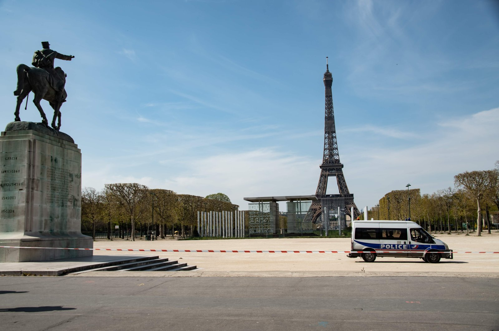 A police van is parked in the closed Jardin du Champs de Mars garden in front of the Eiffel tower in Paris, France, Tuesday, April 7, 2020. (AFP Photo)