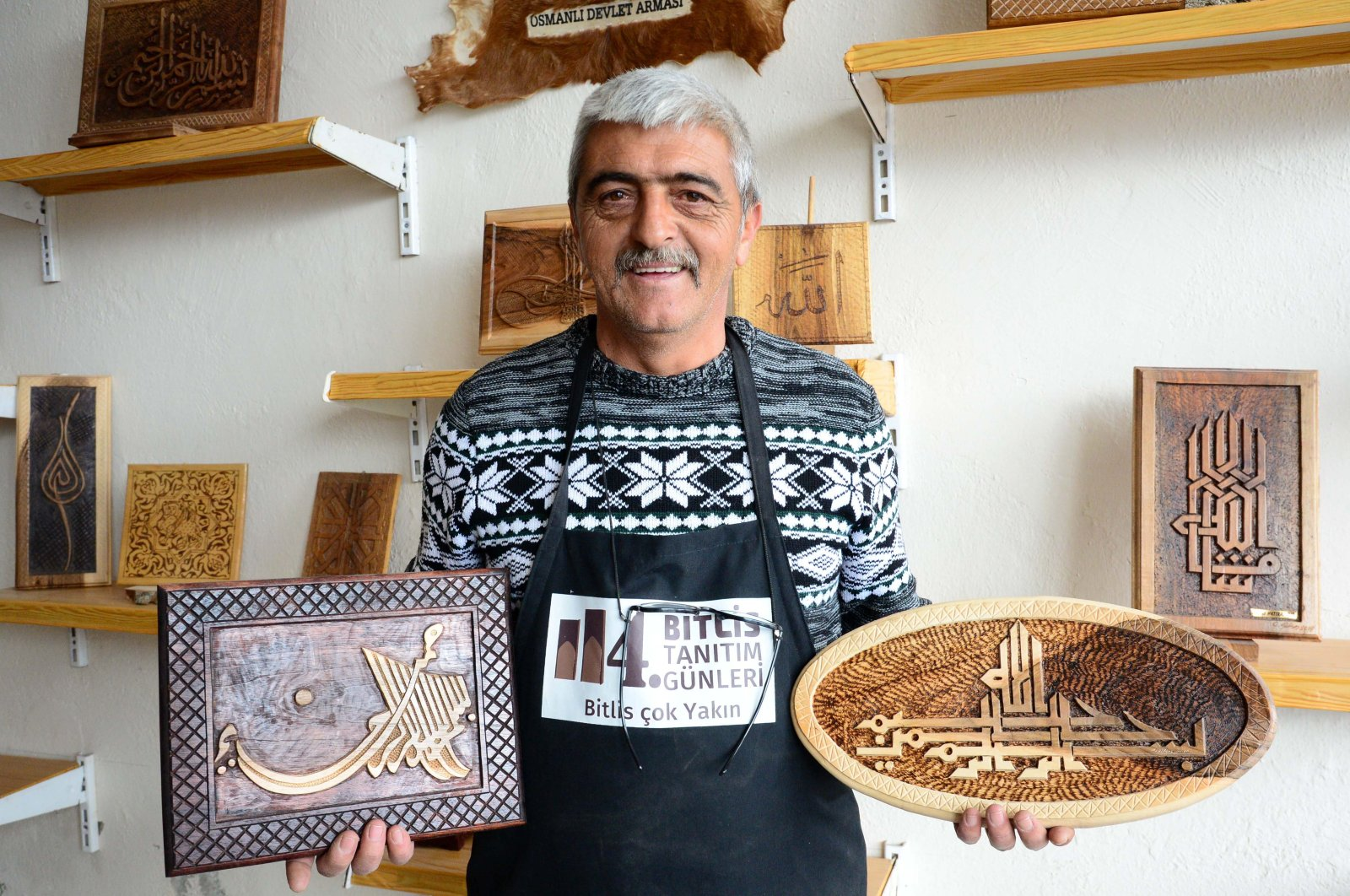 In this undated photo, Osman Gülsar poses with some of his works at his workshop in Bitlis, Turkey. (AA Photo)