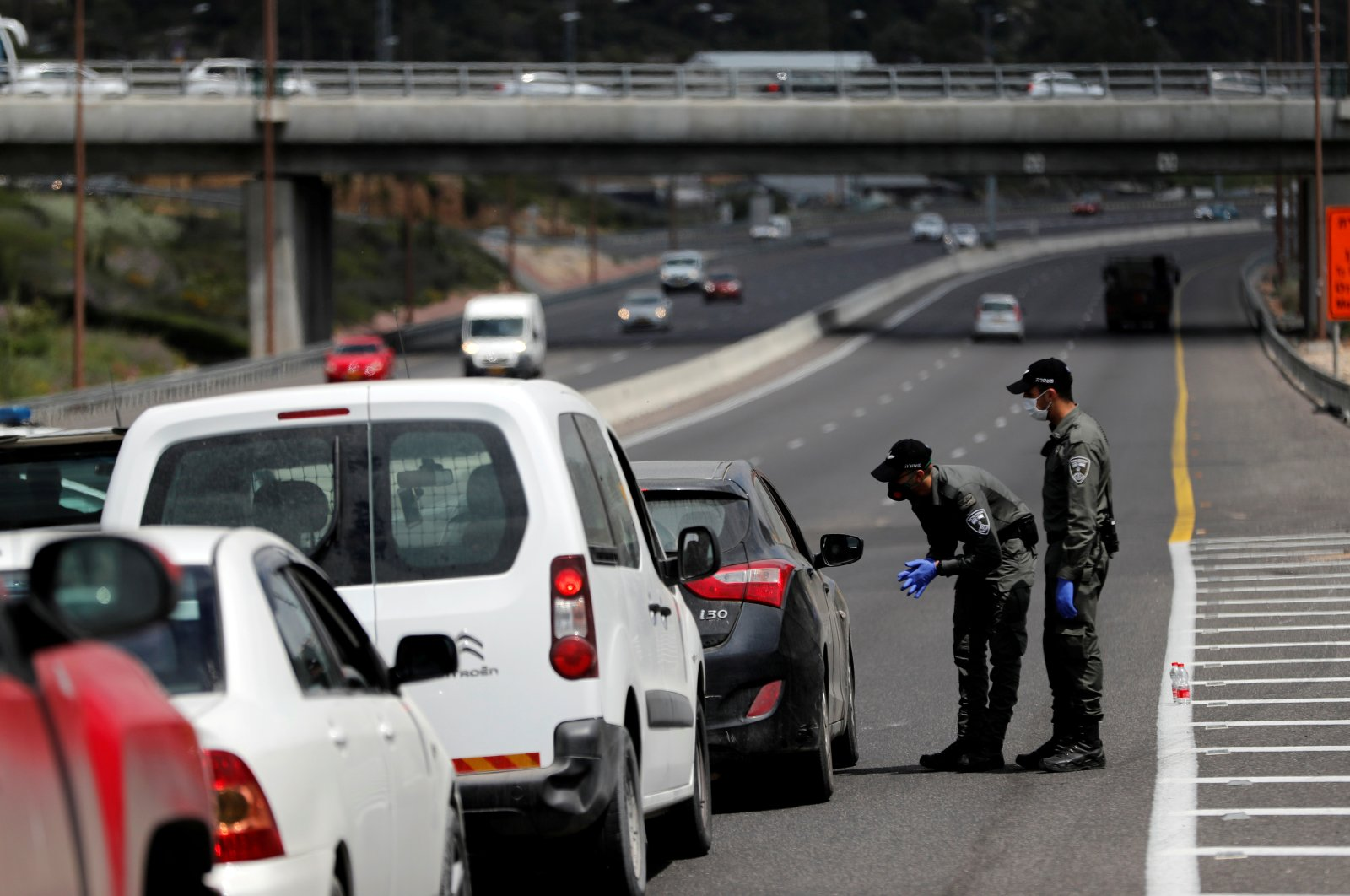 Border policemen chat with a driver at a roadblock set up by police as they begin to enforce a national lockdown to fight the spread of the coronavirus, on a road leading to Jerusalem, near Ein Hemed, Israel, Tuesday, April 7, 2020. (AP Photo)