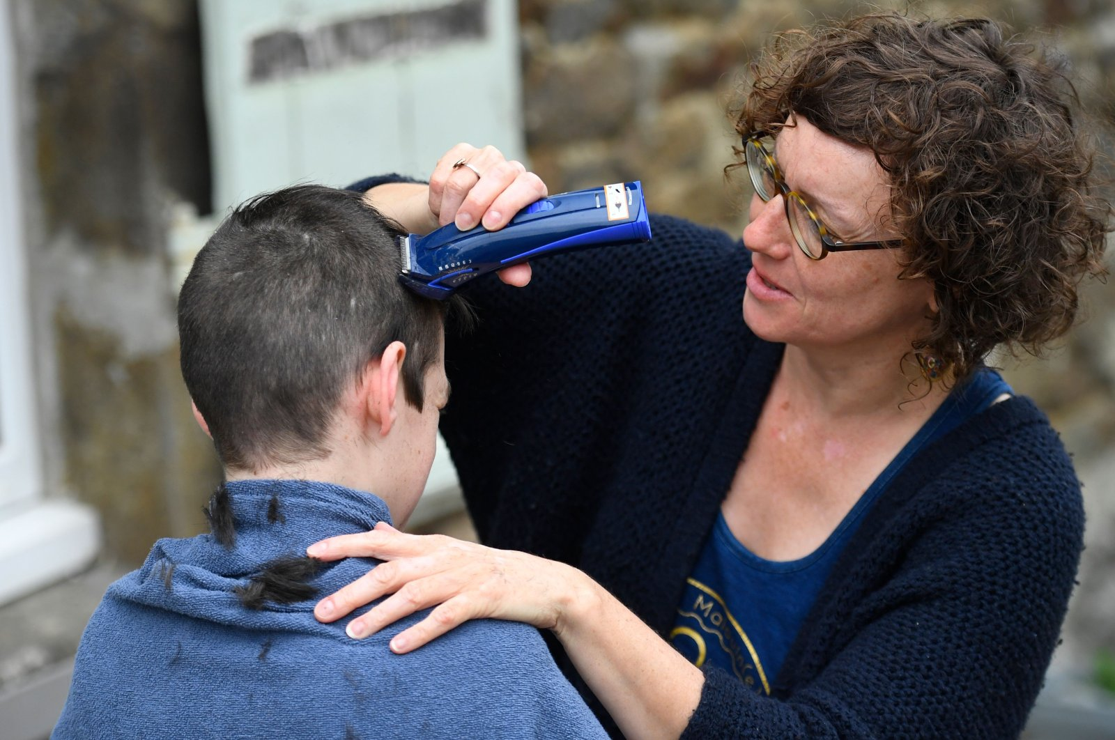 A woman gives her 13-year-old son a haircut outside their home in Hede-Bazouges, Brittany, April 7, 2020. (AFP Photo)