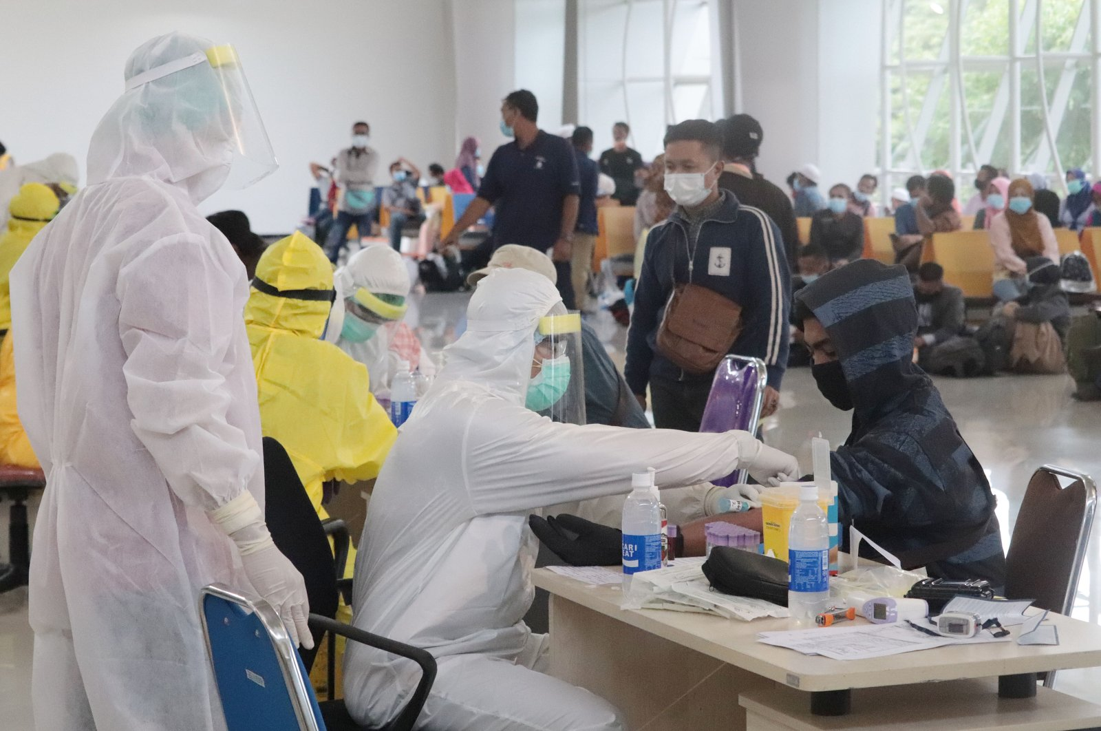 Health care professionals carry out health checks at Juanda International Airport in East Java's capital Surabaya, Indonesia, Tuesday, April 7, 2020. (AA Photo)