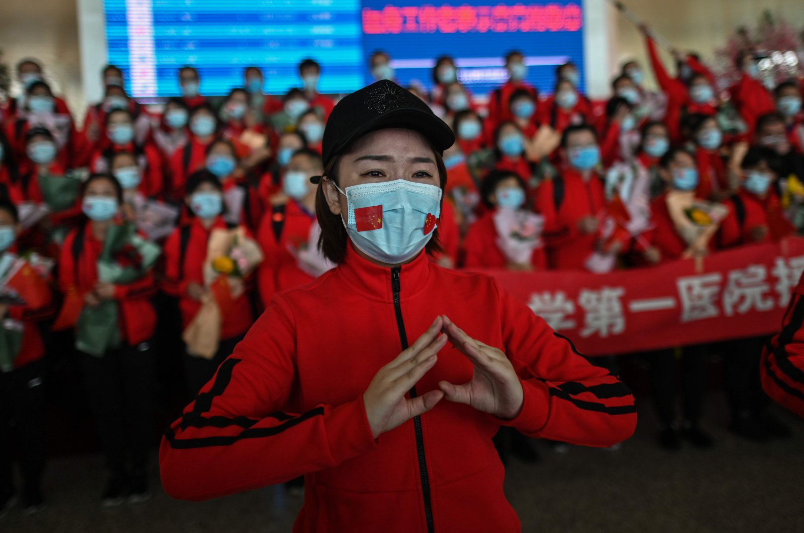 A medical worker from Jilin province tears up during a ceremony as Tianhe Airport is reopened in Wuhan, Hubei province, China, Wednesday, April 8, 2020. (AFP Photo)