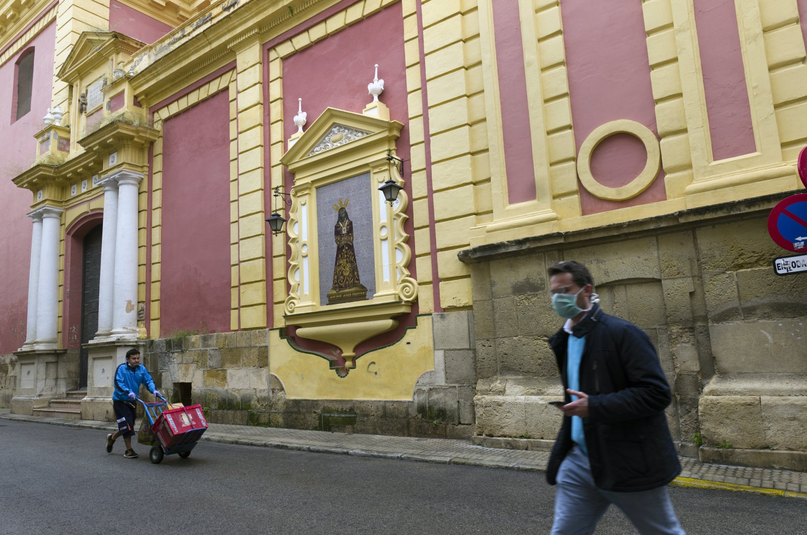A delivery man walks past a large picture of Jesus Christ after a Holy Week procession was canceled due to the coronavirus outbreak in Seville, Spain, Tuesday, April 7, 2020. (AP Photo)
