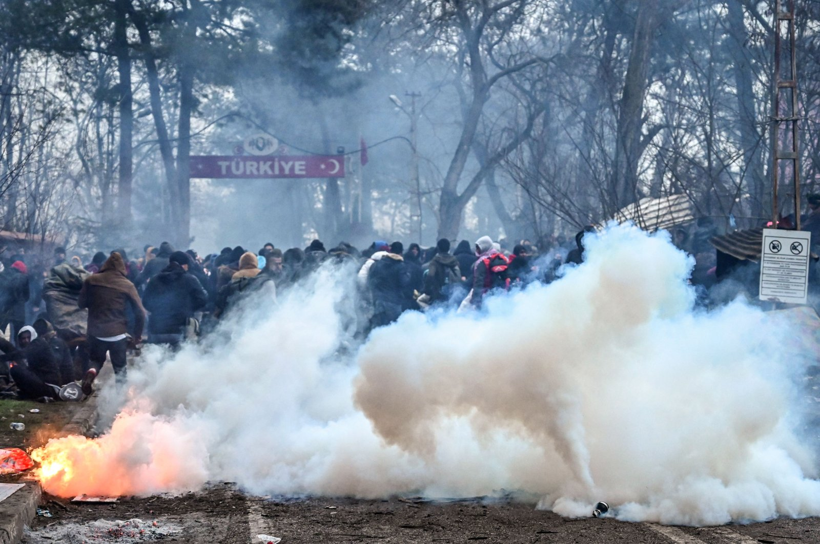 Migrants run away as Greek anti-riot police officers use tear gas in the buffer zone at the Turkey-Greece border, at Pazarkule, Turkey's Edirne province, Feb. 29, 2020. (AFP Photo)