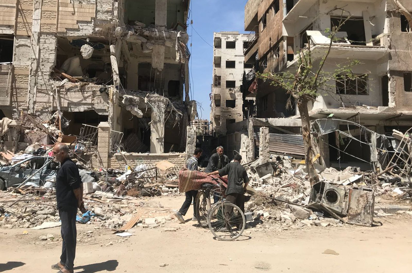 People stand in front of damaged buildings, in the town of Douma, the site of a suspected chemical weapons attack, near Damascus, Syria, Monday, April 16, 2018. (AP Photo)