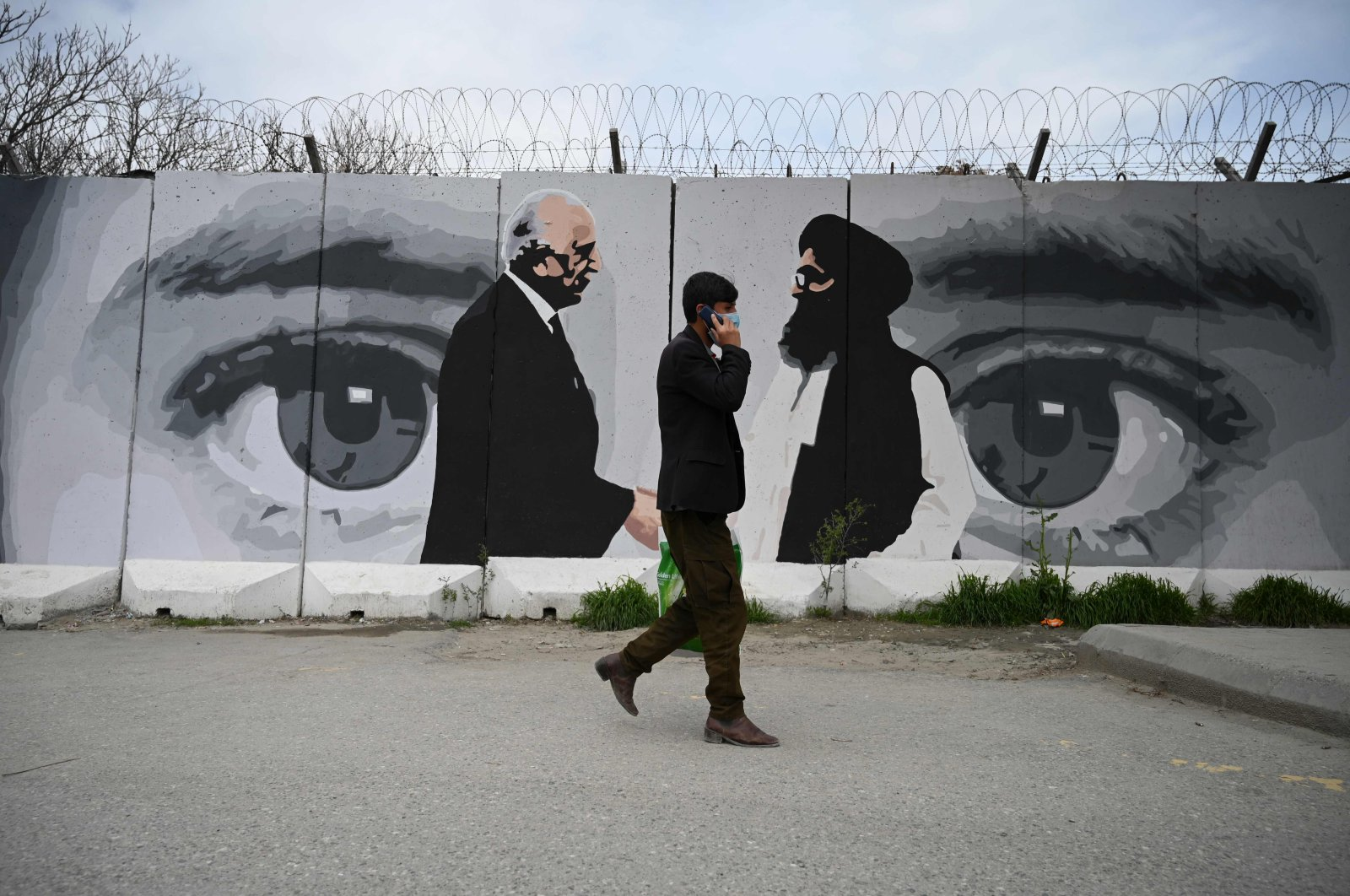 A man wearing a face mask walks past a wall painted with images of U.S. Special Representative for Afghanistan Reconciliation Zalmay Khalilzad (L) and Taliban co-founder Mullah Abdul Ghani Baradar (R), in Kabul, Sunday, April 5, 2020. (AFP Photo)