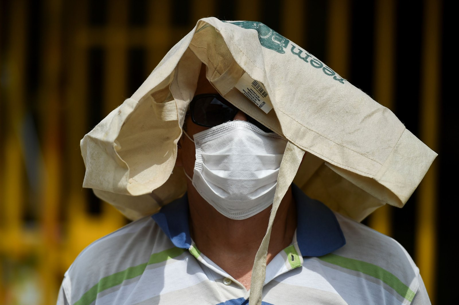 A man wears a face mask as a preventive measure against the spread of the novel coronavirus, COVID-19, as he lines up outside a supermarket in Cali, Colombia, on April 6, 2020. (AFP Photo)