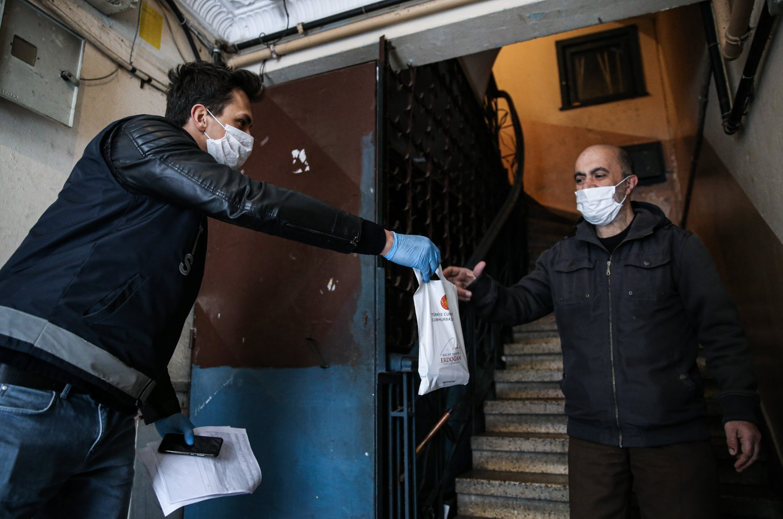 A police officer delivers a bag of masks and cologne to a citizen in Istanbul, Turkey, Wednesday, April 8, 2020. (AA Photo)