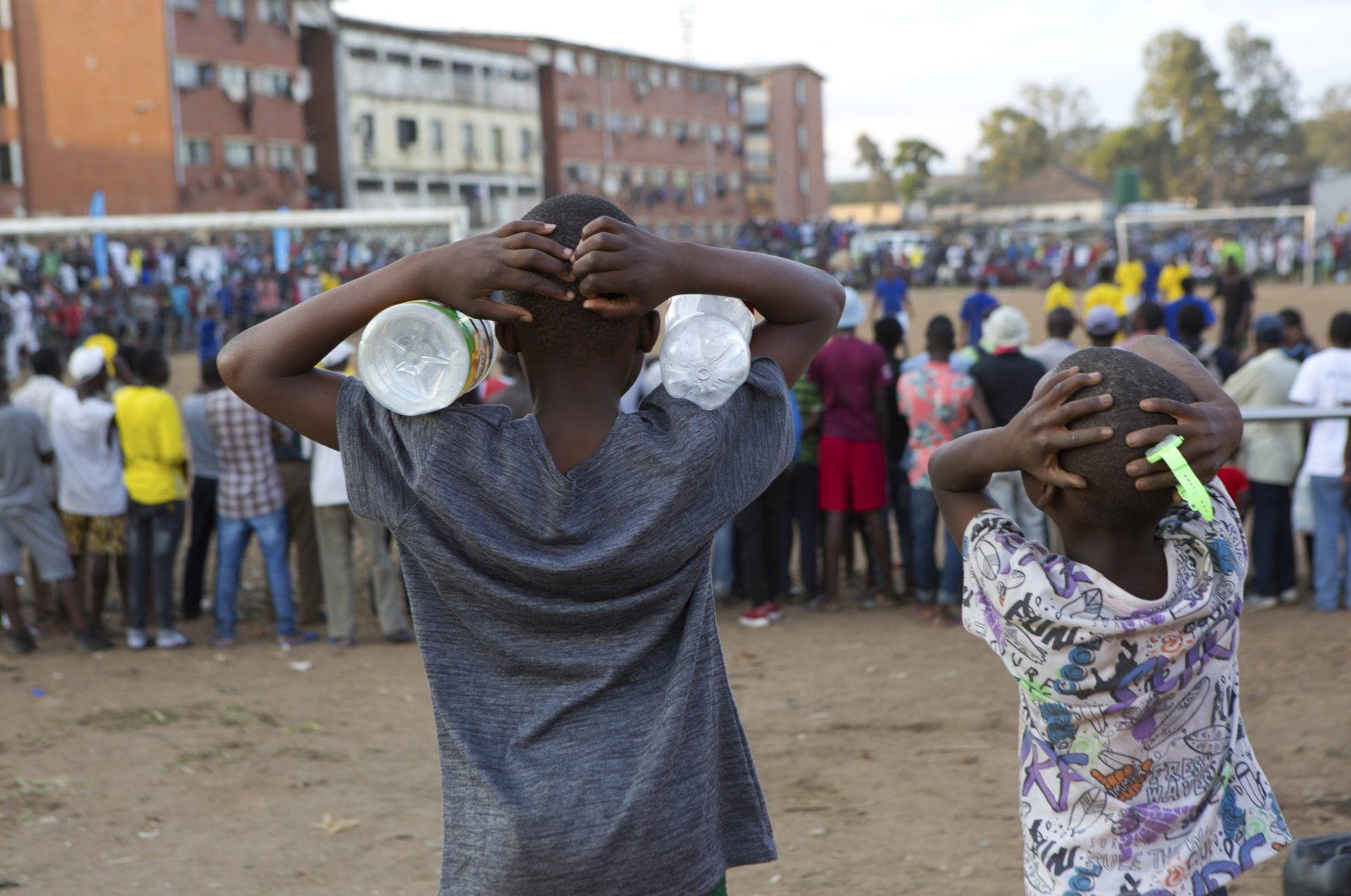 Children react while watching a soccer match in Harare, Zimbabwe, Sunday, March 15, 2020. (AP Photo)