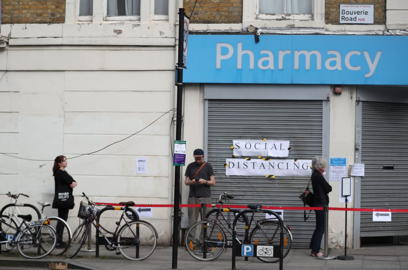People are seen following social distancing rules as they queue outside a pharmacy in Stoke Newington, London, April 8, 2020. (REUTERS Photo)