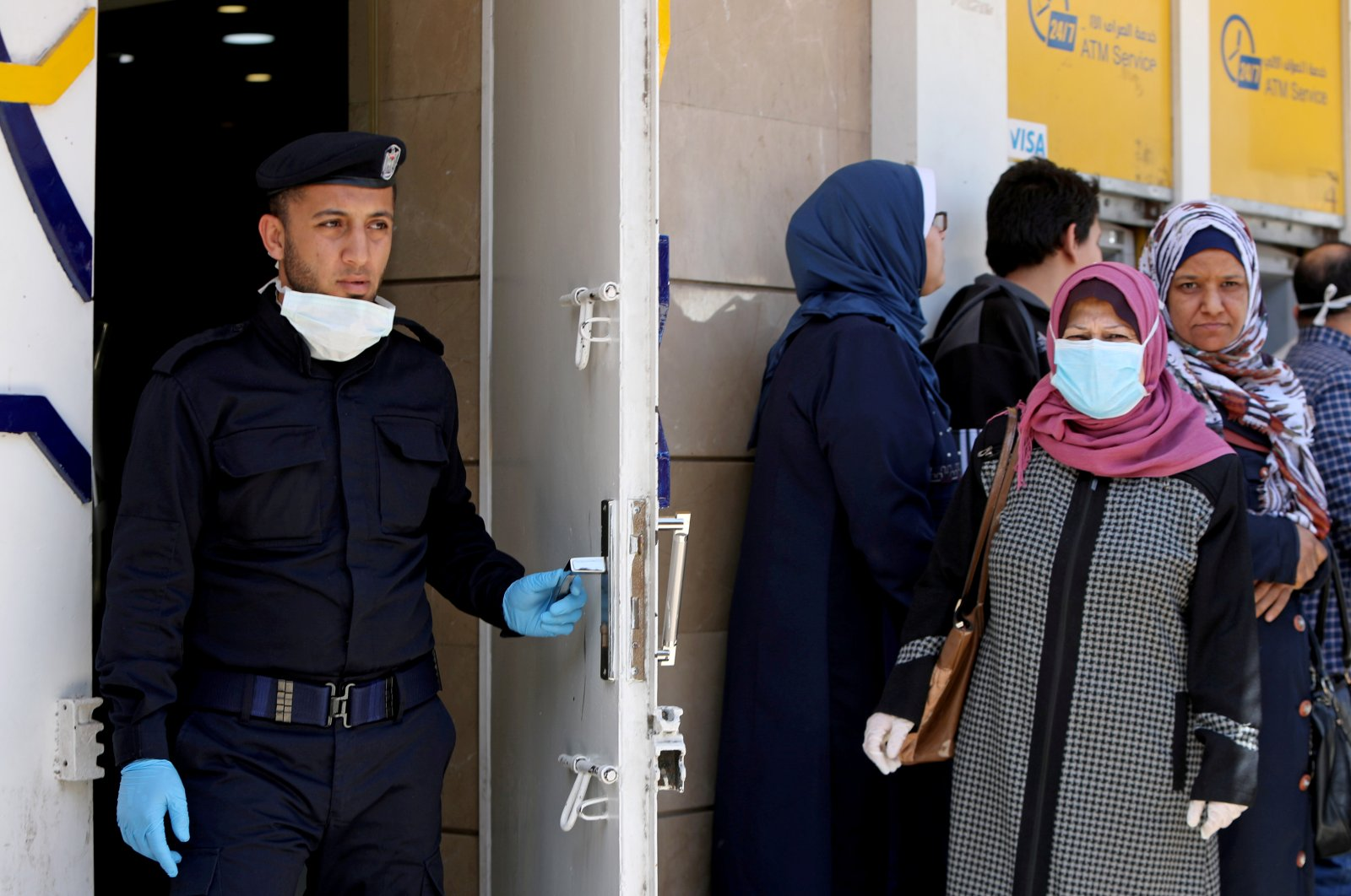 A Palestinian policeman stands guard as a woman, wearing a mask as a precaution against the coronavirus disease, waits with other people outside a bank to withdraw cash, Gaza City, March 29, 2020. (REUTERS Photo)