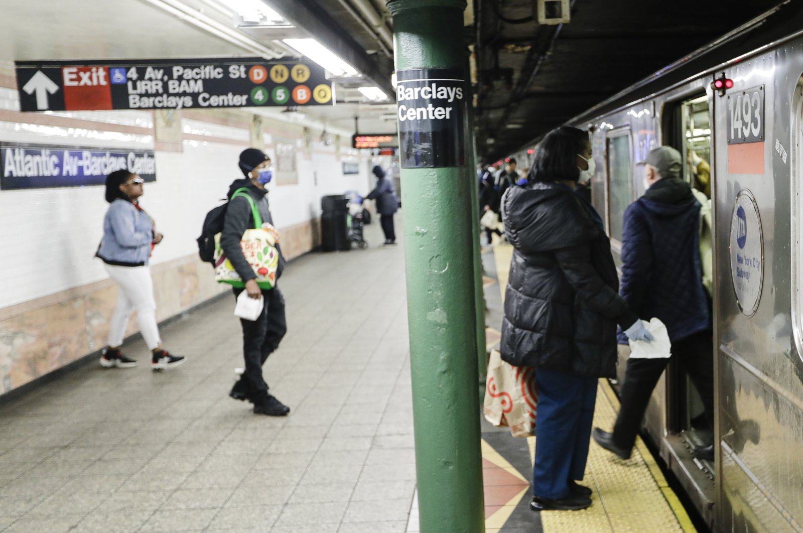 Patrons, wearing masks, board a train at the Atlantic Avenue station in the Brooklyn borough of New York, Tuesday, April 7, 2020. (AP Photo)