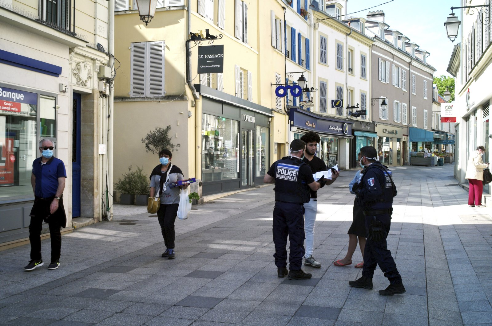Municipal police officers check documents as they patrol in a street of Sceaux during nationwide confinement measures to counter the COVID-19, in Sceaux, south of Paris, Wednesday, April 8, 2020 (AP Photo)