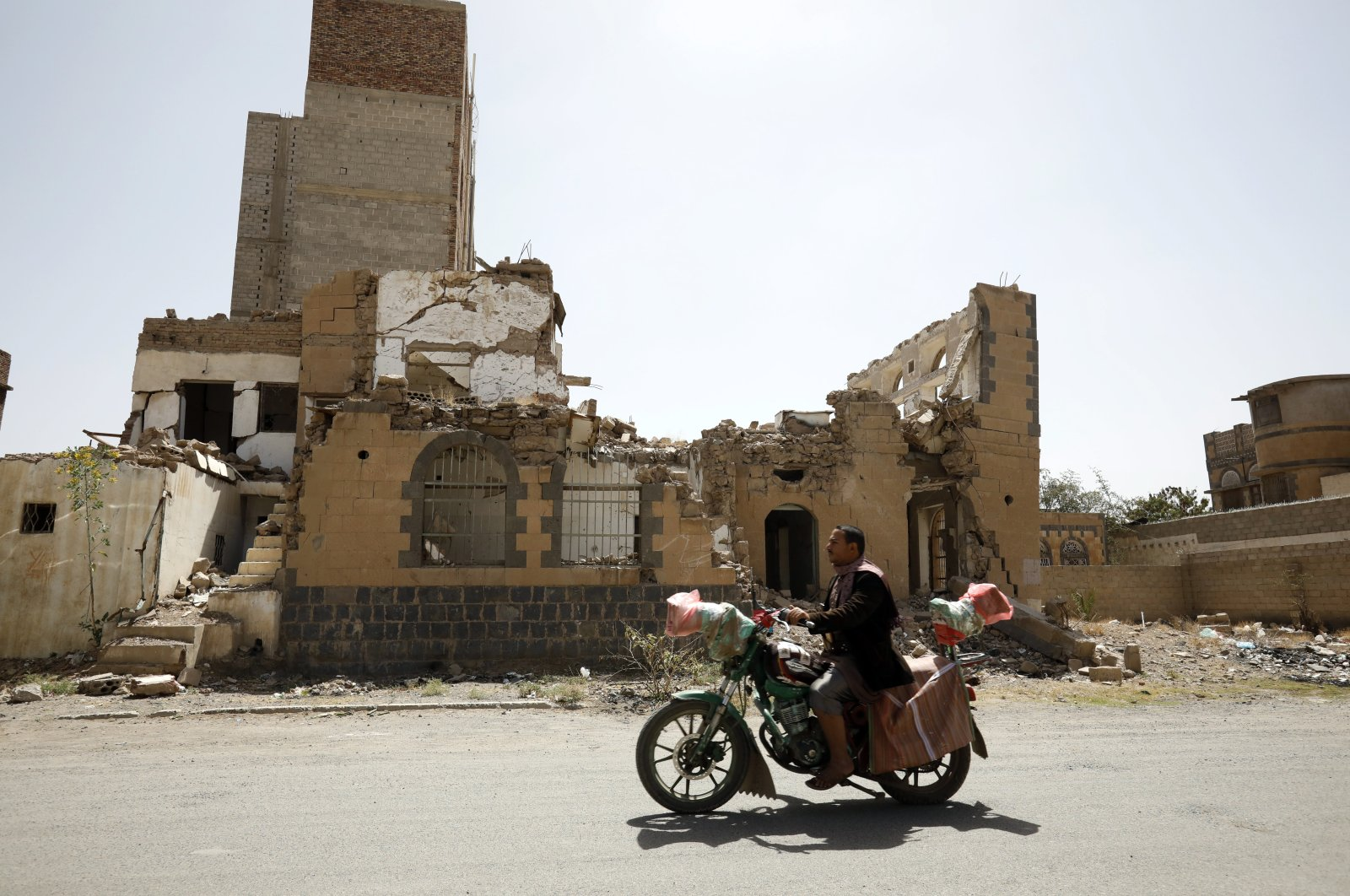 A Yemeni rides a motorbike past a destroyed building targeted by a Saudi-led airstrike at a neighborhood in Sanaa, Yemen, March 26, 2020. (EPA Photo)