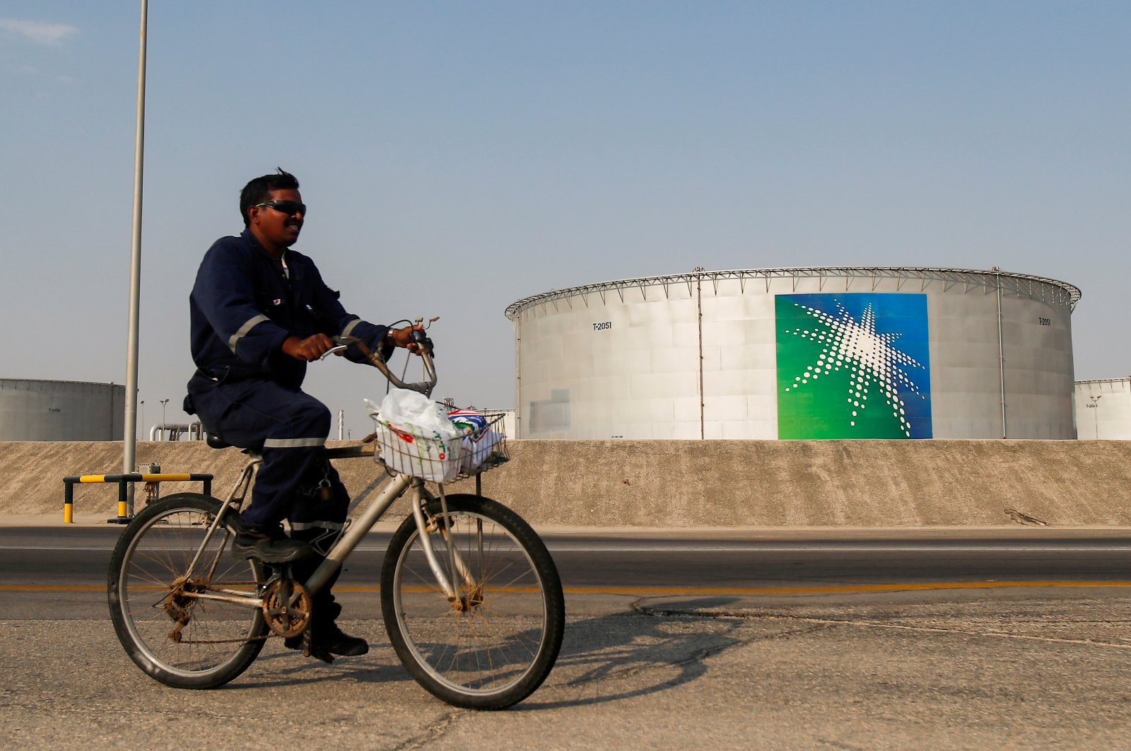 An employee rides a bicycle next to oil tanks at the Saudi Aramco oil facility in Abqaiq, Saudi Arabia, Oct. 12, 2019. (Reuters Photo)