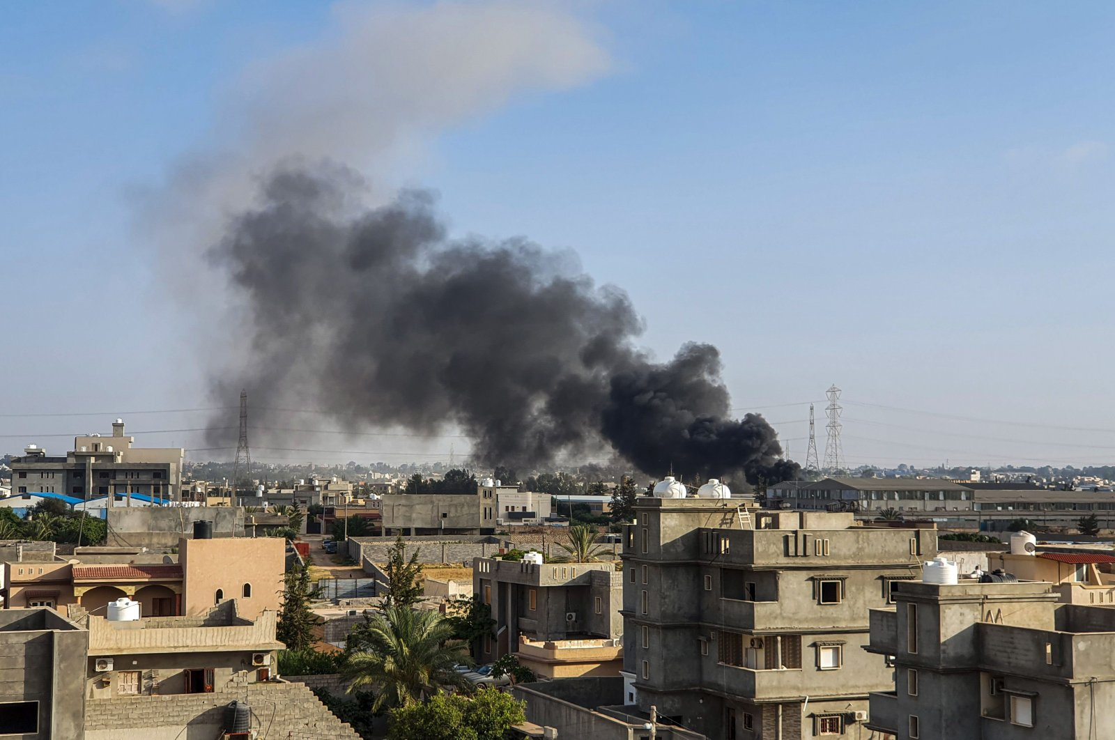 This picture taken on June 29, 2019, shows smoke plumes rising in Tajoura, south of the Libyan capital Tripoli, following a reported airstrike by forces loyal to warlord Khalifa Haftar. (AFP Photo)
