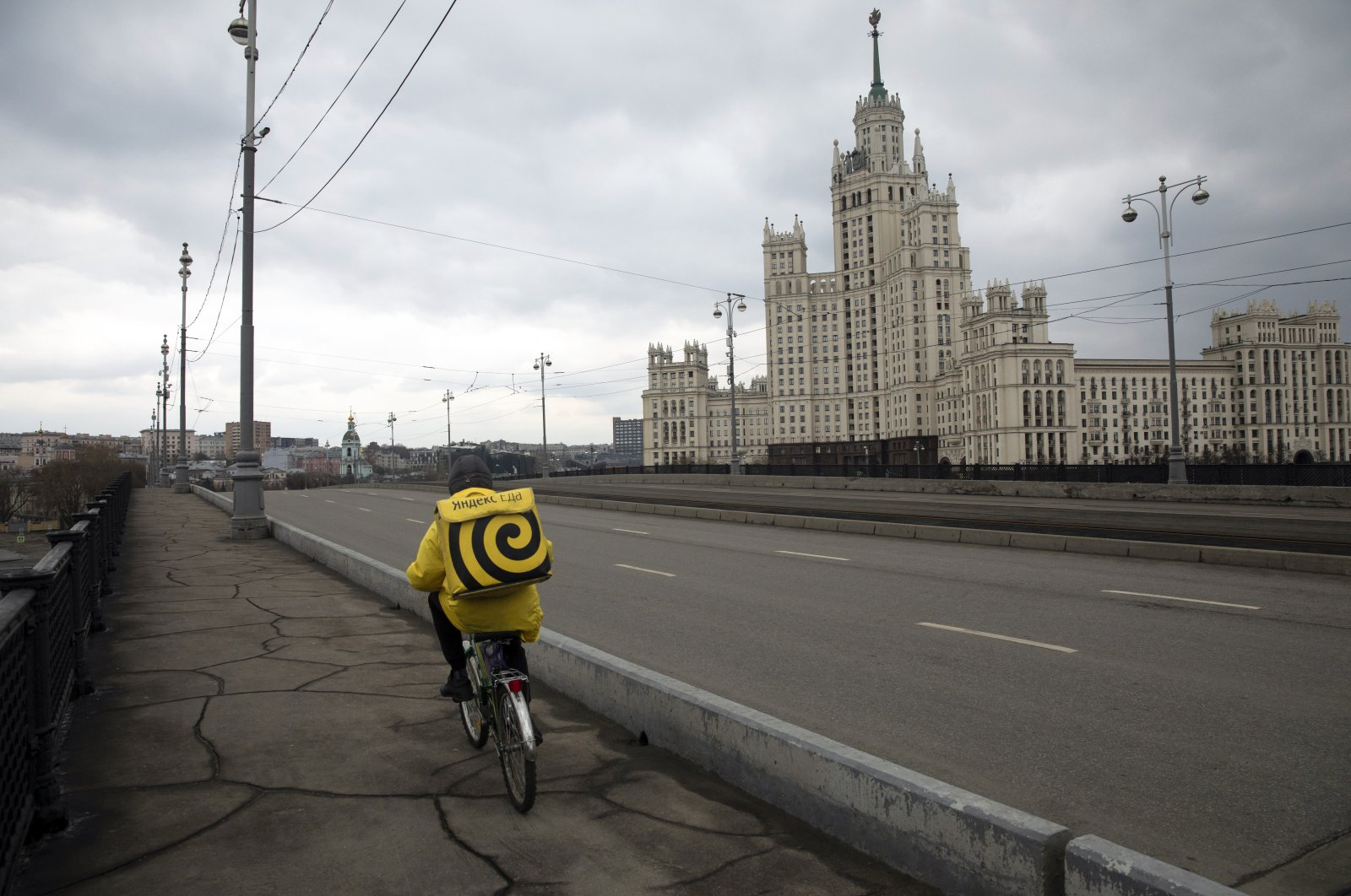 A food delivery courier crosses the bridge over the Moskva River, with the Kotelnicheskaya Embankment Building in the background, Moscow, Russia, April 8, 2020. (AP Photo)