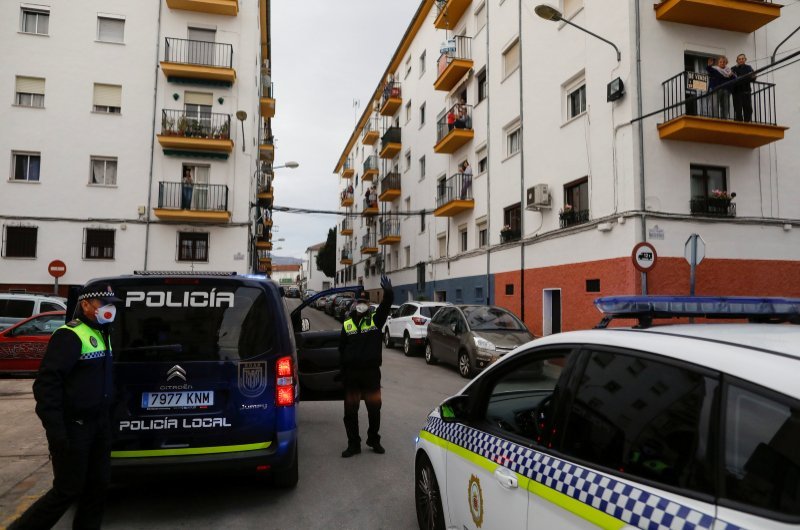 A police officer greets people as they look on from their balconies amid the coronavirus outbreak, in Ronda, southern Spain, April 8, 2020. (Reuters Photo)