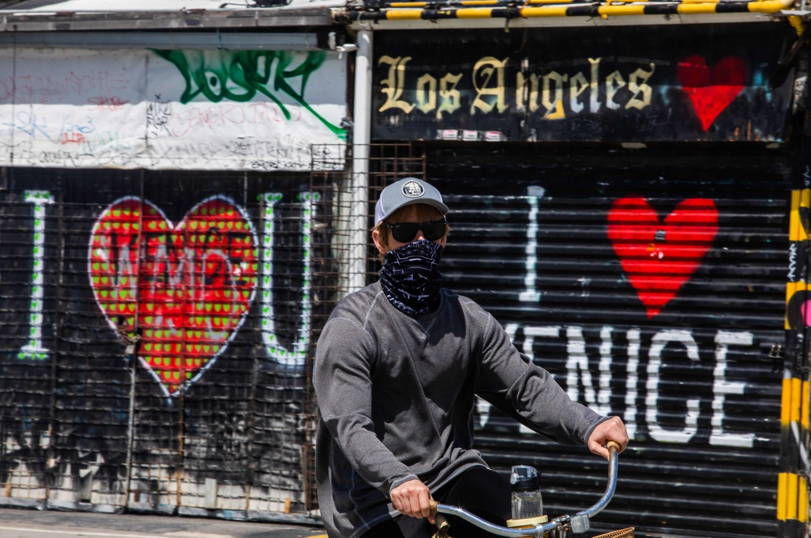 A man wearing a scarf as a face mask rides his bike during the coronavirus pandemic, in Venice Beach, Los Angeles, California, U.S., April 4, 2020. (AFP Photo)