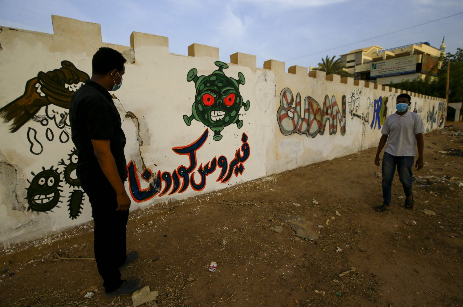 Sudanese volunteers, wearing protective face masks, stand next to a graffiti of the COVID-19, Khartoum, April 8, 2020. (AFP Photo)