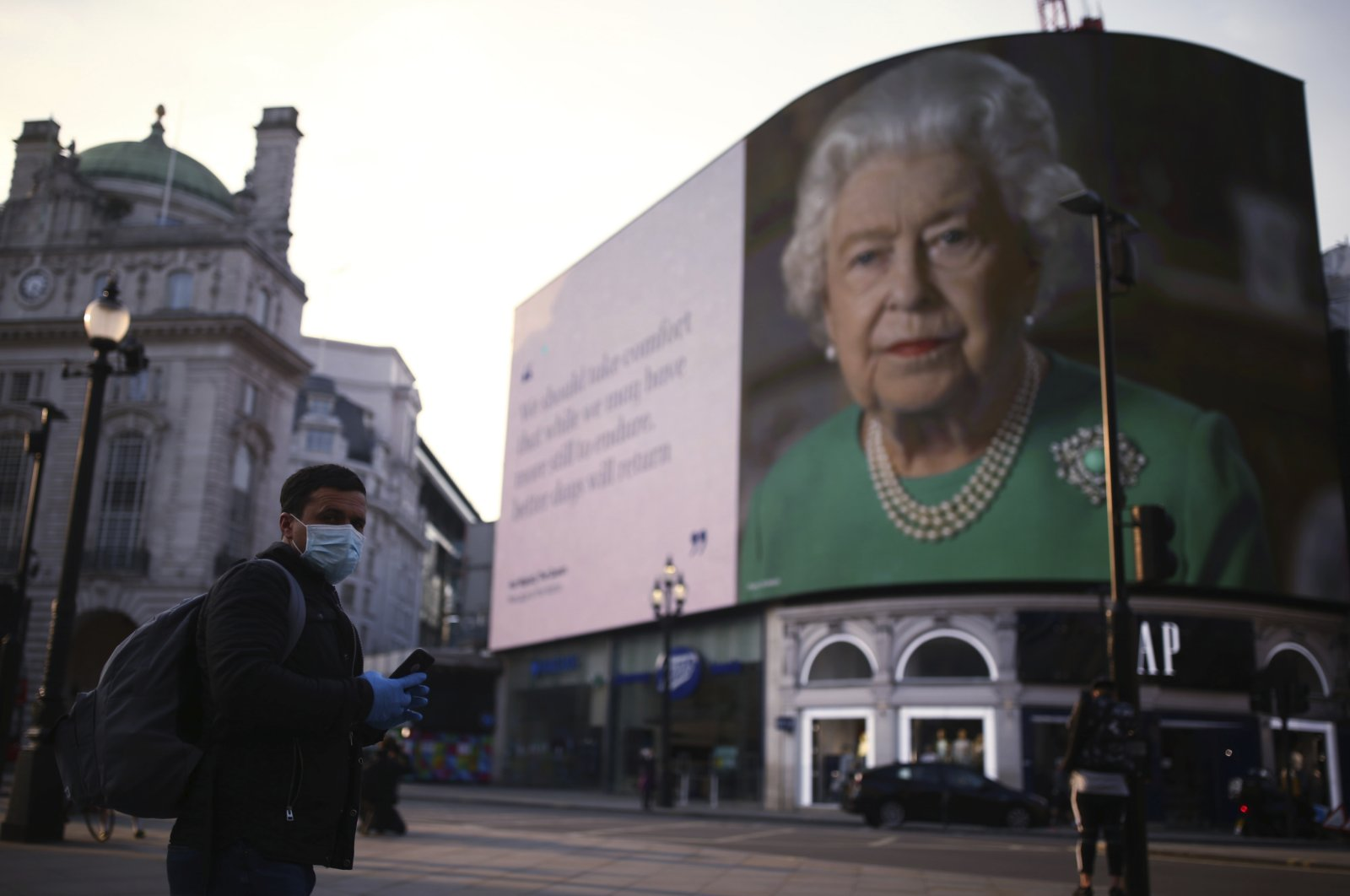 An image of Queen Elizabeth II and quotes from her historic TV broadcast commenting on the coronavirus epidemic are displayed at Piccadilly Circus in London, April 8, 2020. (AP Photo)