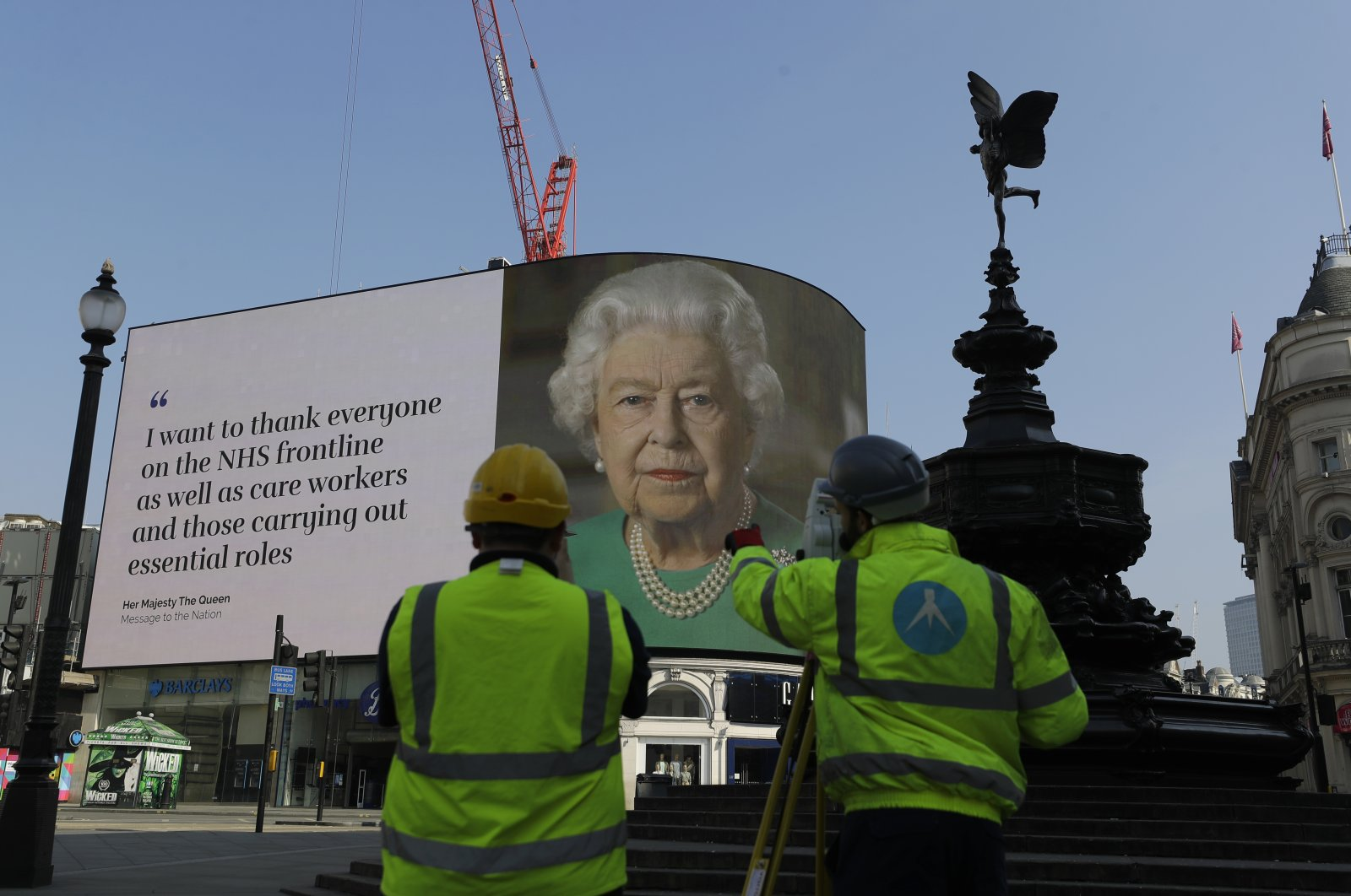 An image of Britain's Queen Elizabeth II and quotes from her historic television broadcast commenting on the coronavirus pandemic are displayed on a big screen behind the Eros statue at Piccadilly Circus in London, April 9, 2020. (AP Photo)