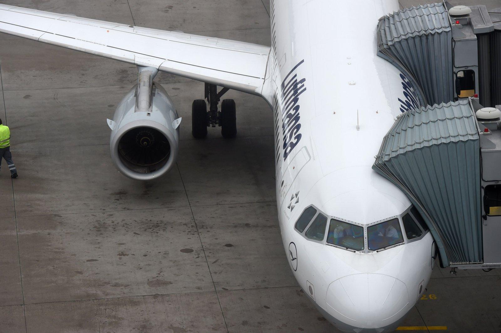 An employee at the Franz-Josef-Strauss airport walks past a plane belonging to German airline Lufthansa, Nov. 24, 2016, Munich. (AFP Photo)