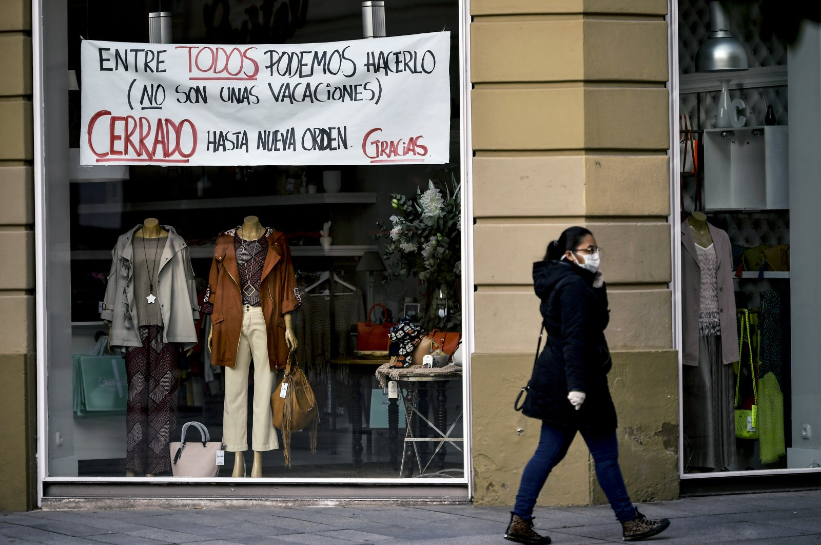 "A woman wearing a face mask walks in front of a store with a banner reading, ""Together we can do it. It's not the holidays. Closed until further notice. Thank you,"" Pamplona, Spain, April 8, 2020. (AP Photo)"