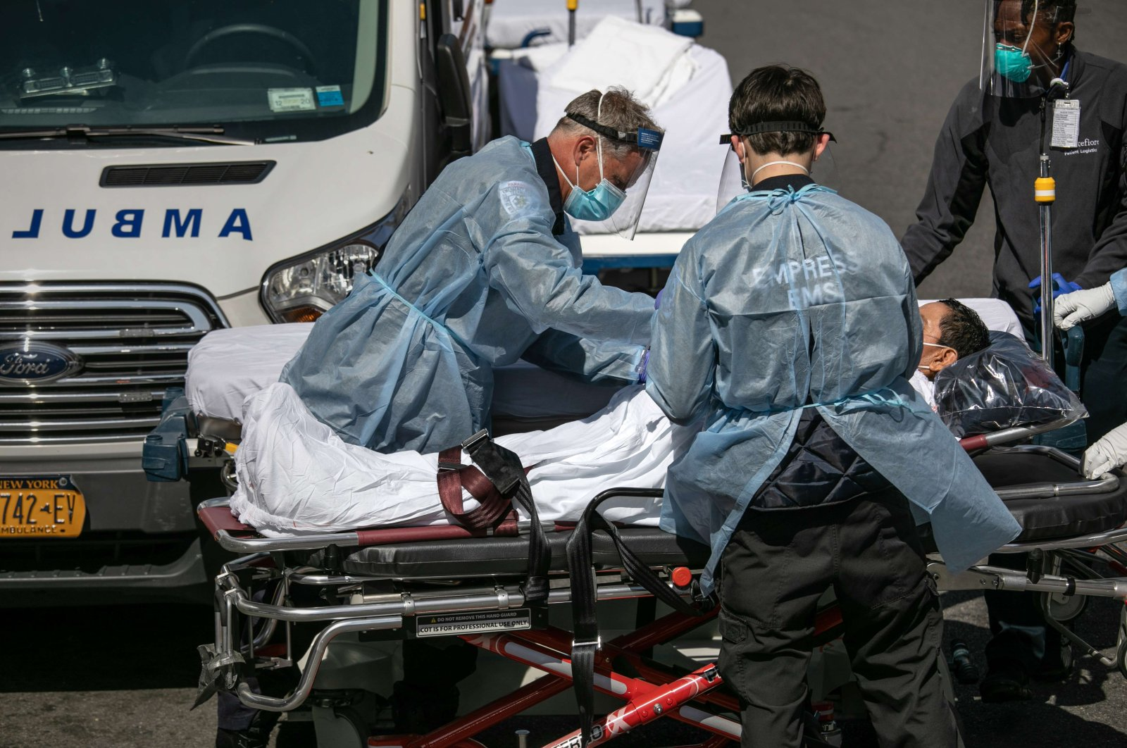 Medics and hospital workers tend to a COVID-19 patient outside the Montefiore Medical Center Moses Campus in the Bronx borough of New York City,  Tuesday, April 07, 2020. (AFP)