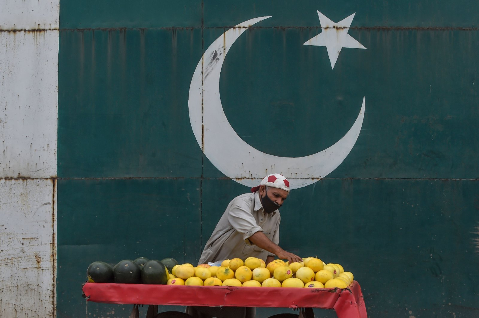 A fruit vendor wearing a facemask waits for customers under a painting of the national flag alongside a street during a government-imposed nationwide lockdown as a preventive measure against the coronavirus, in Lahore, Thursday, April 9, 2020. (AFP)