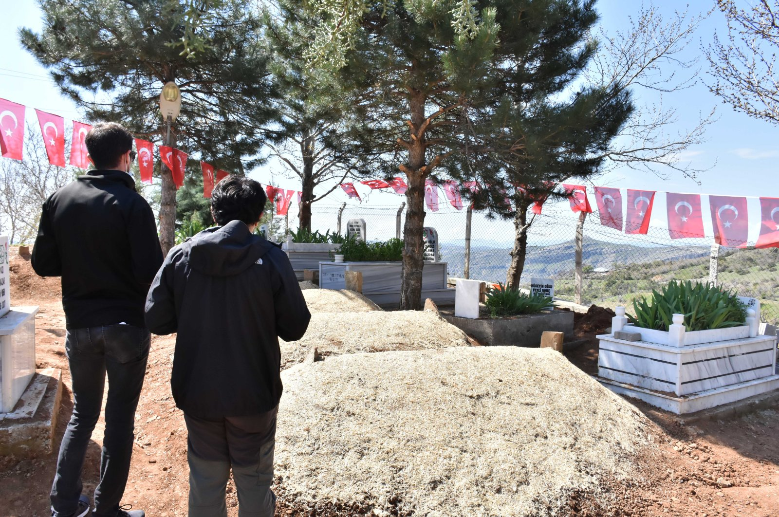 Two men pray by the graveside of victims, in Diyarbakır, Turkey, Thursday, April 9, 2020. (AA Photo)