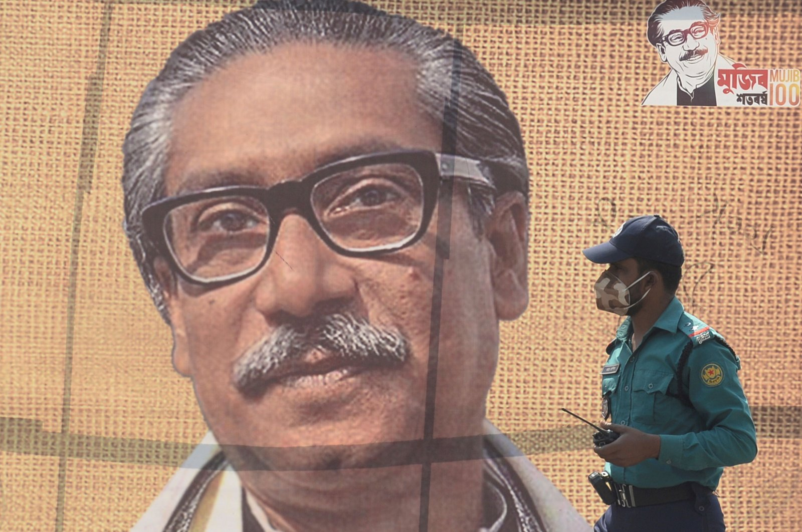A policeman wearing a facemask amid fears of the spread of coronavirus walks past a banner with a picture of Bangladesh's founder Sheikh Mujibur Rahman in Dhaka,  March 09, 2020. (AFP)
