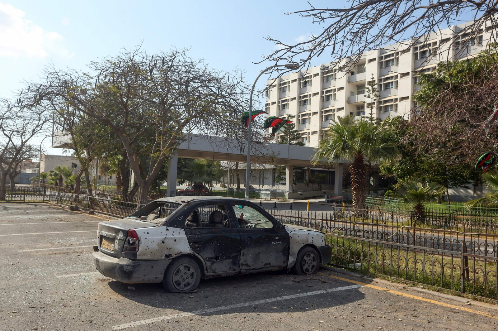 A burnt-out car is seen at the parking lot of Khadra General Hospital which is dedicated to treating people infected with coronavirus (COVID-19) in the Libyan capital Tripoli, Wednesday, April 8, 2020. (AFP)