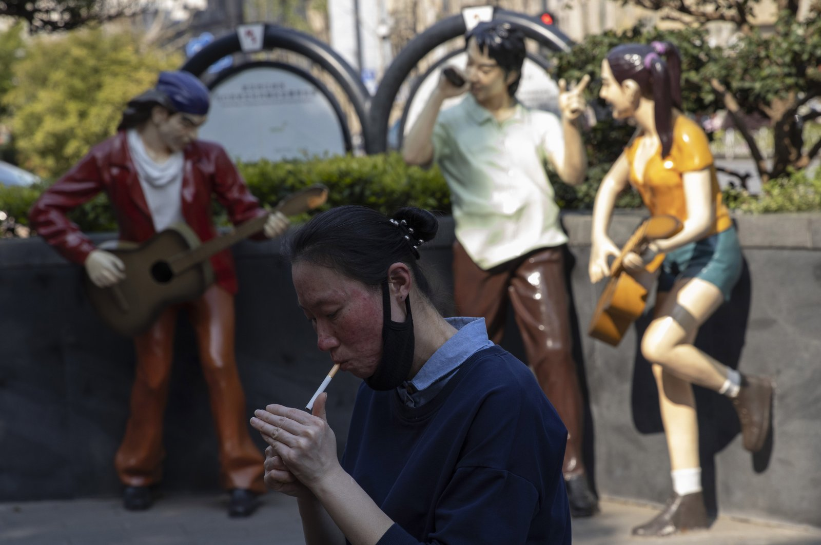A resident lowers for mask for a smoke near statues depicting normal life in Wuhan in central China's Hubei province, Thursday, April 9, 2020.  (AP)