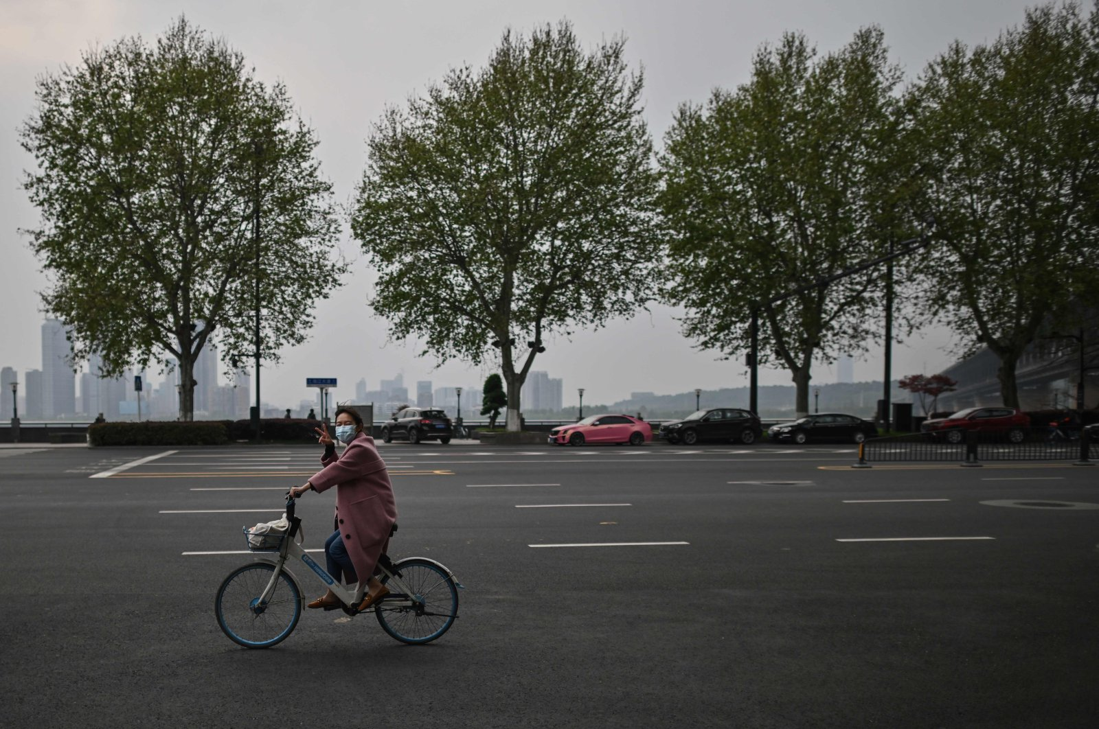 A woman wearing a face mask rides a bicycle next to Wuhan bridge in Wuhan, central Hubei province, China, April 5, 2020. (AFP Photo)