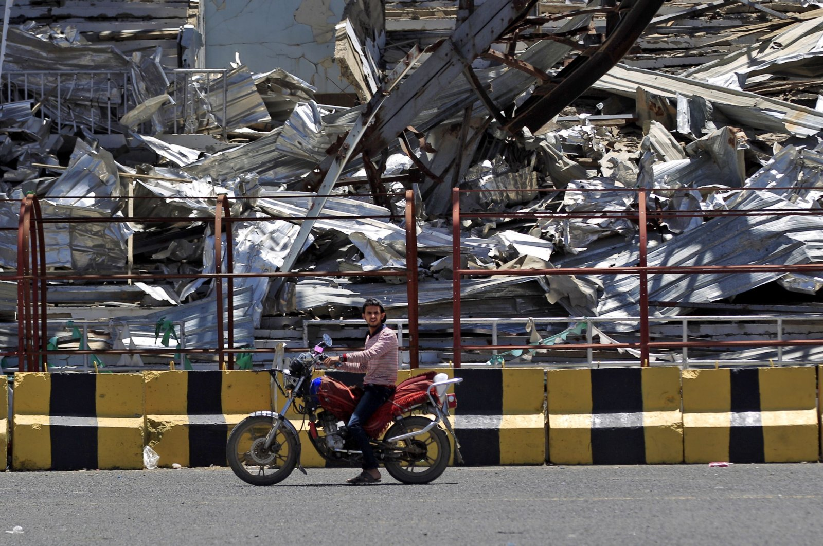 A man drives his motorcycle past a popular public square, which was destroyed in late 2017 in an airstrike by the Saudi-led coalition, Sanaa, Yemen, April 9, 2020. (AFP Photo)