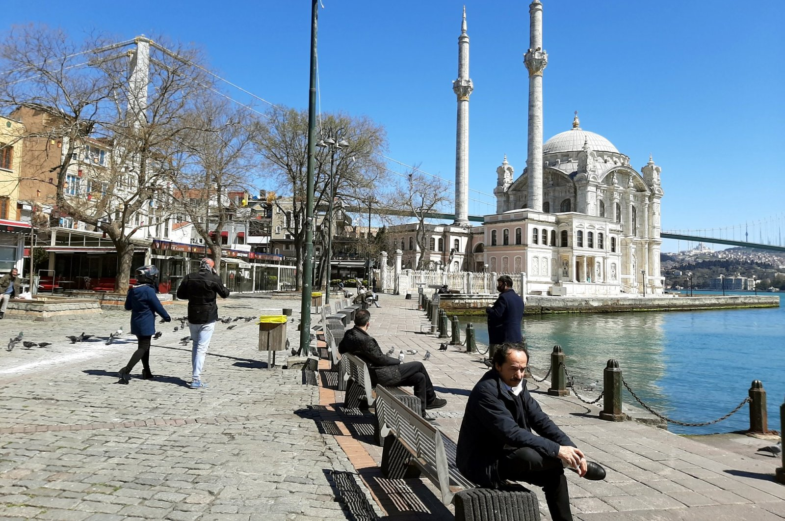 People sit on the benches in Ortaköy, Istanbul, Turkey, April 9, 2020. (Photo by Mustafa Kaya)