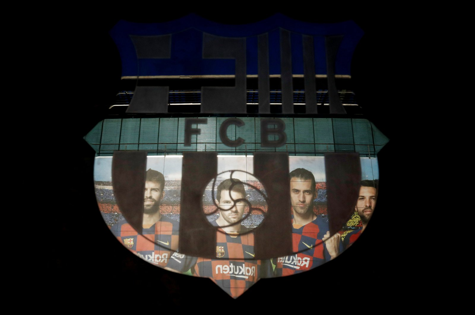 A picture of Lionel Messi with teammates is reflected in the Barcelona emblem outside the stadium before a match, March 7, 2020. (Reuters Photo)