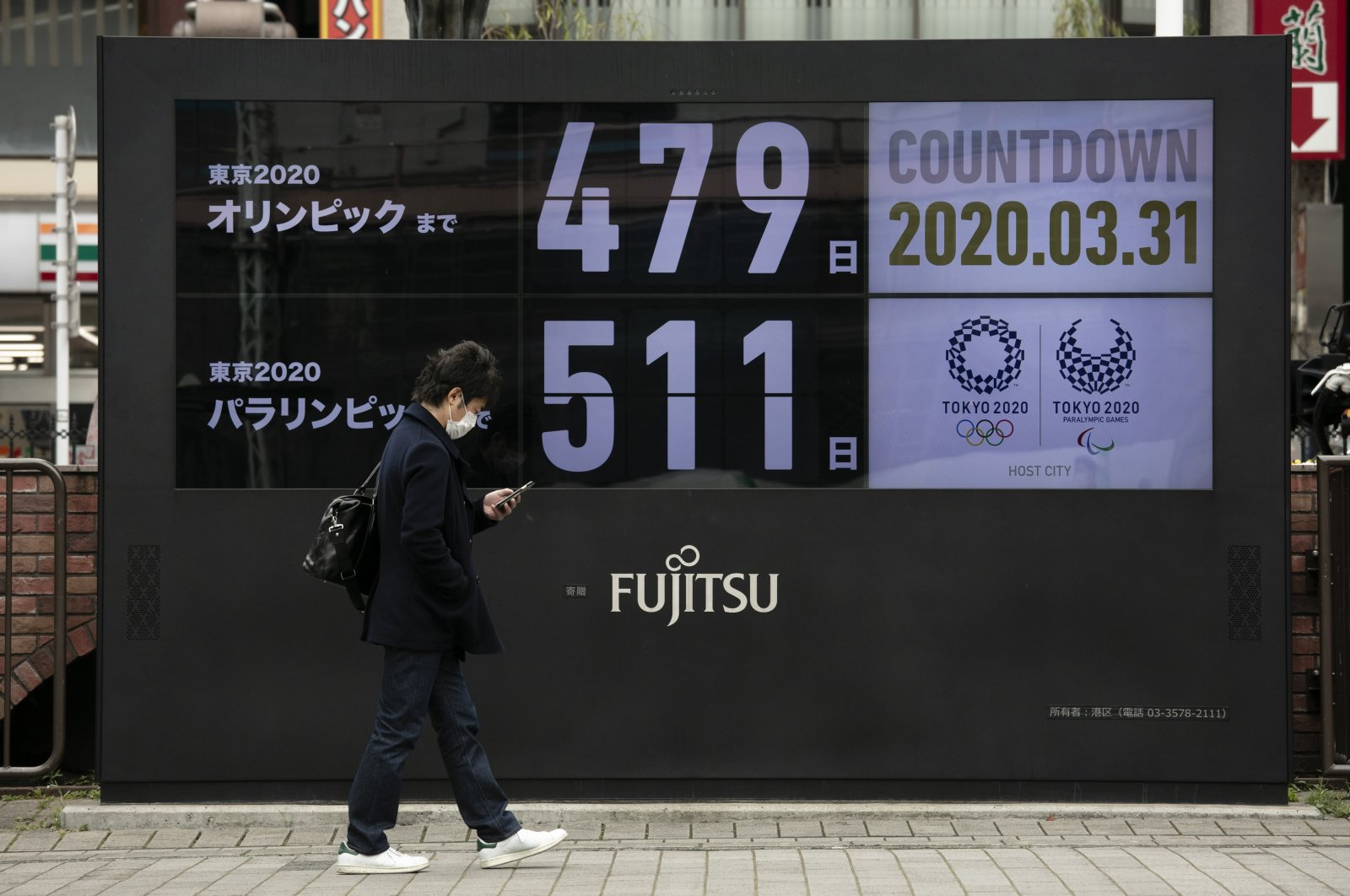 A man walks past a countdown display for the Tokyo 2020 Olympics and Paralympics, Tokyo, March 31, 2020. (AP Photo)