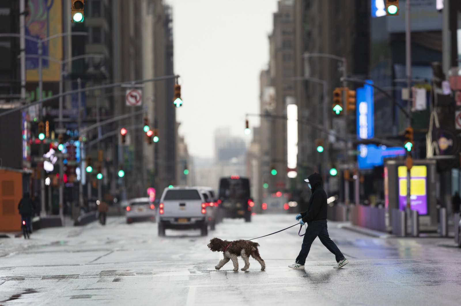 A man wearing a mask walks his dog through a quiet Times Square during the coronavirus epidemic in New York, April 9, 2020. (AP Photo)