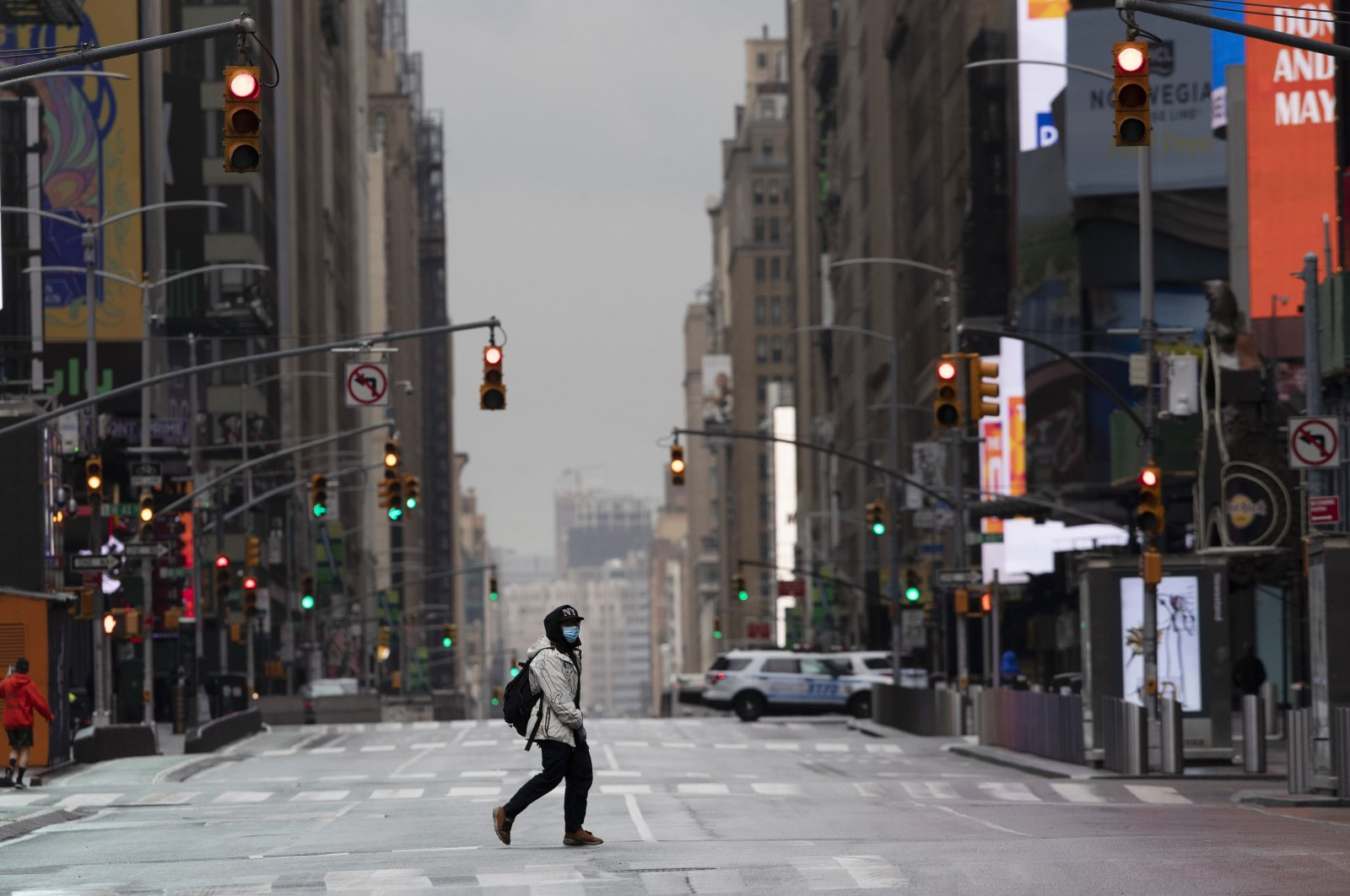 A man wearing a mask crosses the street in an empty Times Square, New York City, April 9, 2020. (AP Photo)