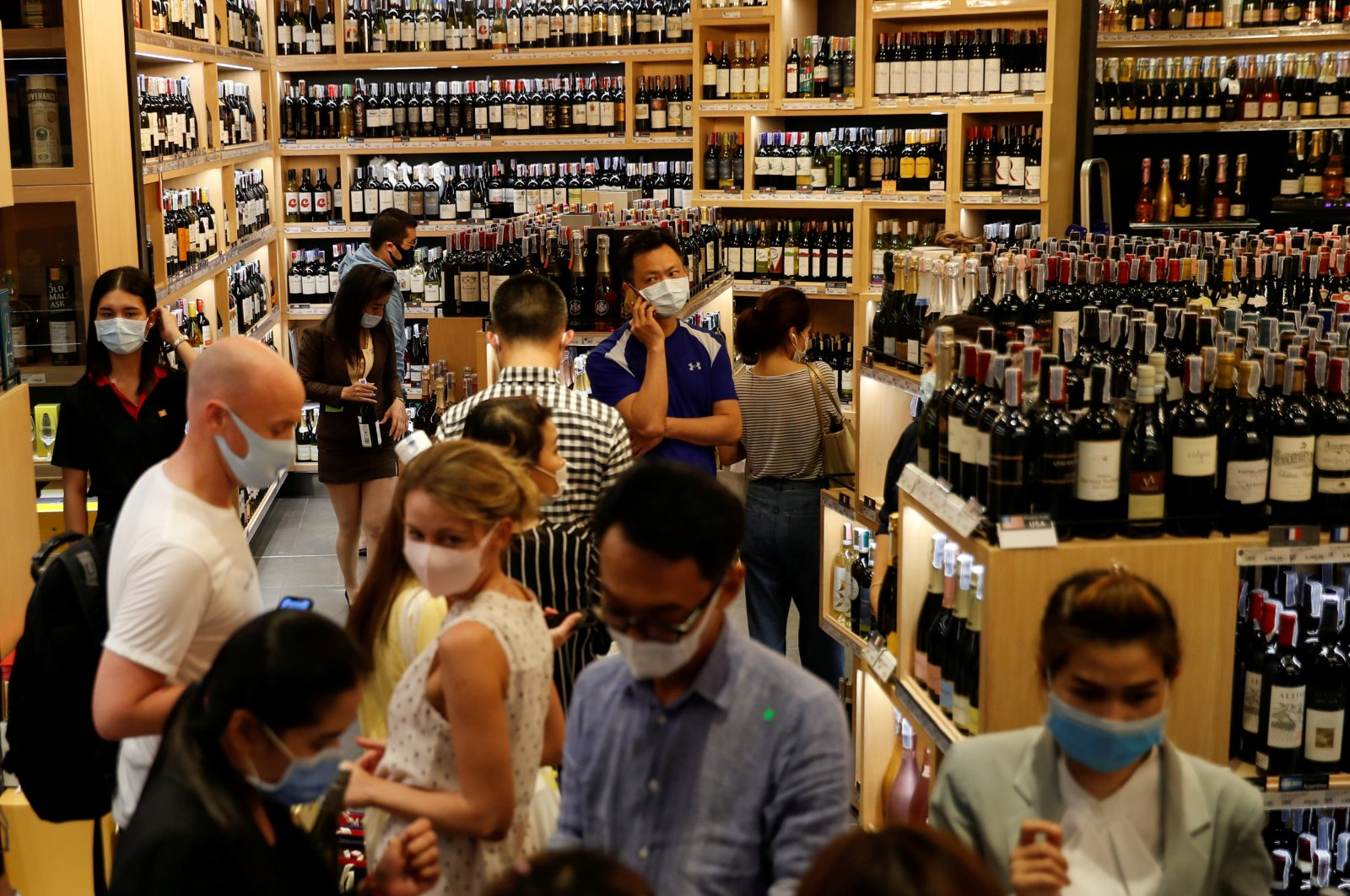 People line up inside a liquor shop after Bangkok and several other provinces announced a 10-day ban on alcohol sale starting April 10 during the coronavirus outbreak in Bangkok, Thailand, April 9, 2020. (Reuters Photo)