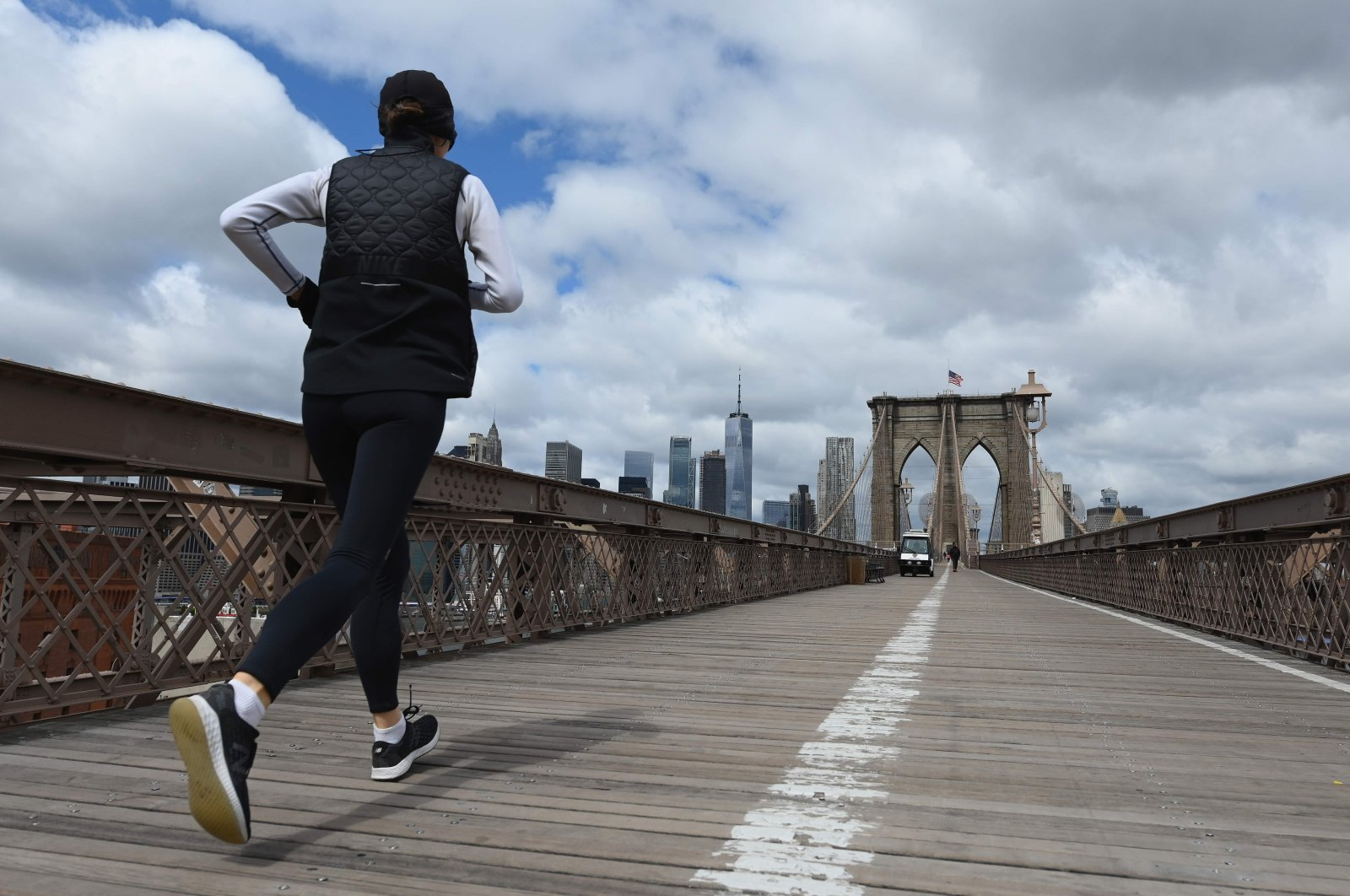 A woman jogs over the nearly empty Brooklyn Bridge in New York City on April 10, 2020. (AFP Photo)